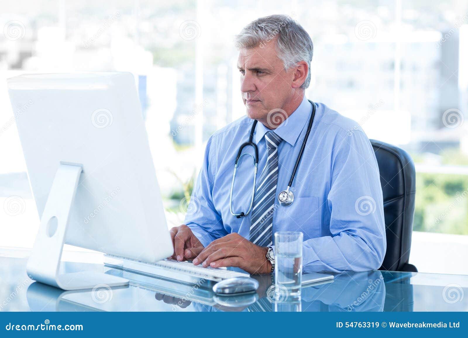 Ernster Doktor, der an Computer an seinem Schreibtisch arbeitet