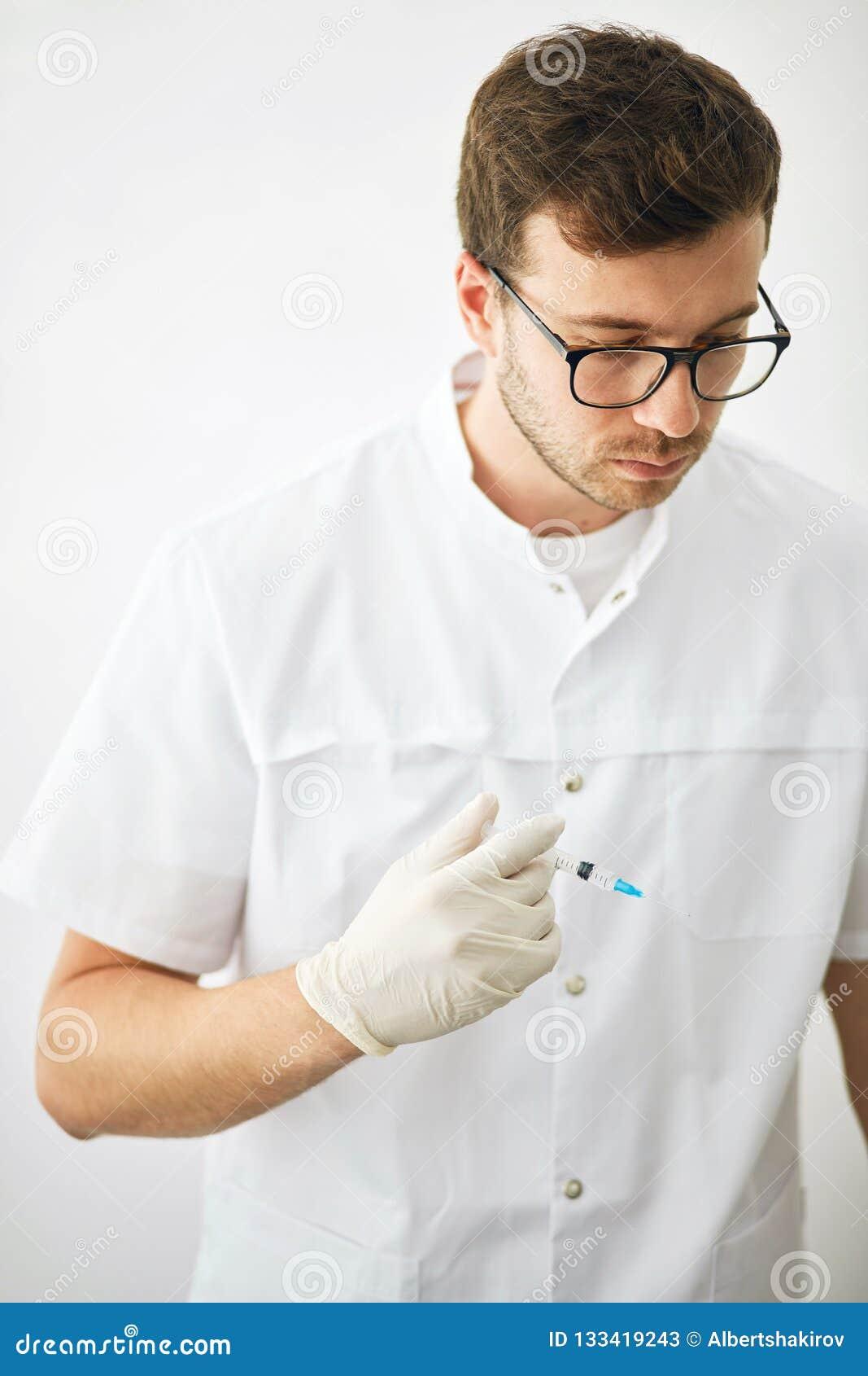 Ernster Doktor mit Medizinschutzimpfungsausrüstung mit Nadel