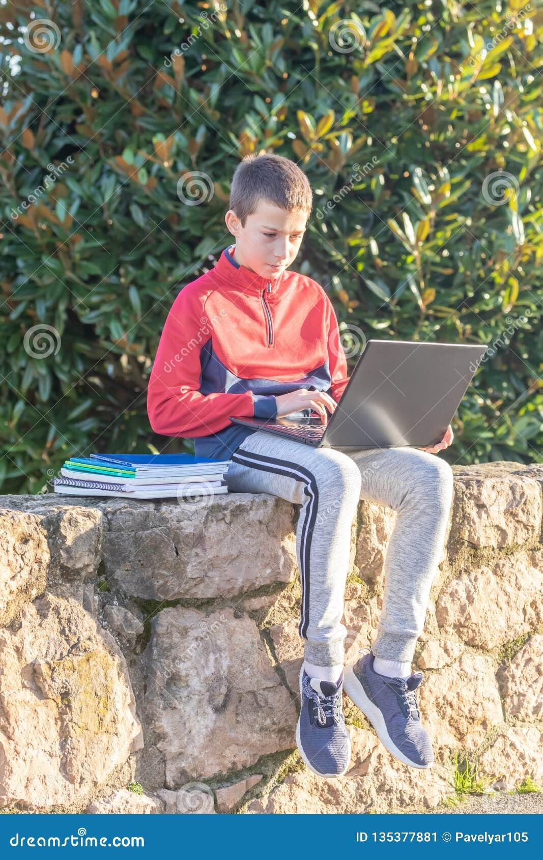 Ernster Jugendlichjunge mit dem Laptop und Lehrbüchern, die Hausarbeit tun und für eine Prüfung im Park sich vorbereiten