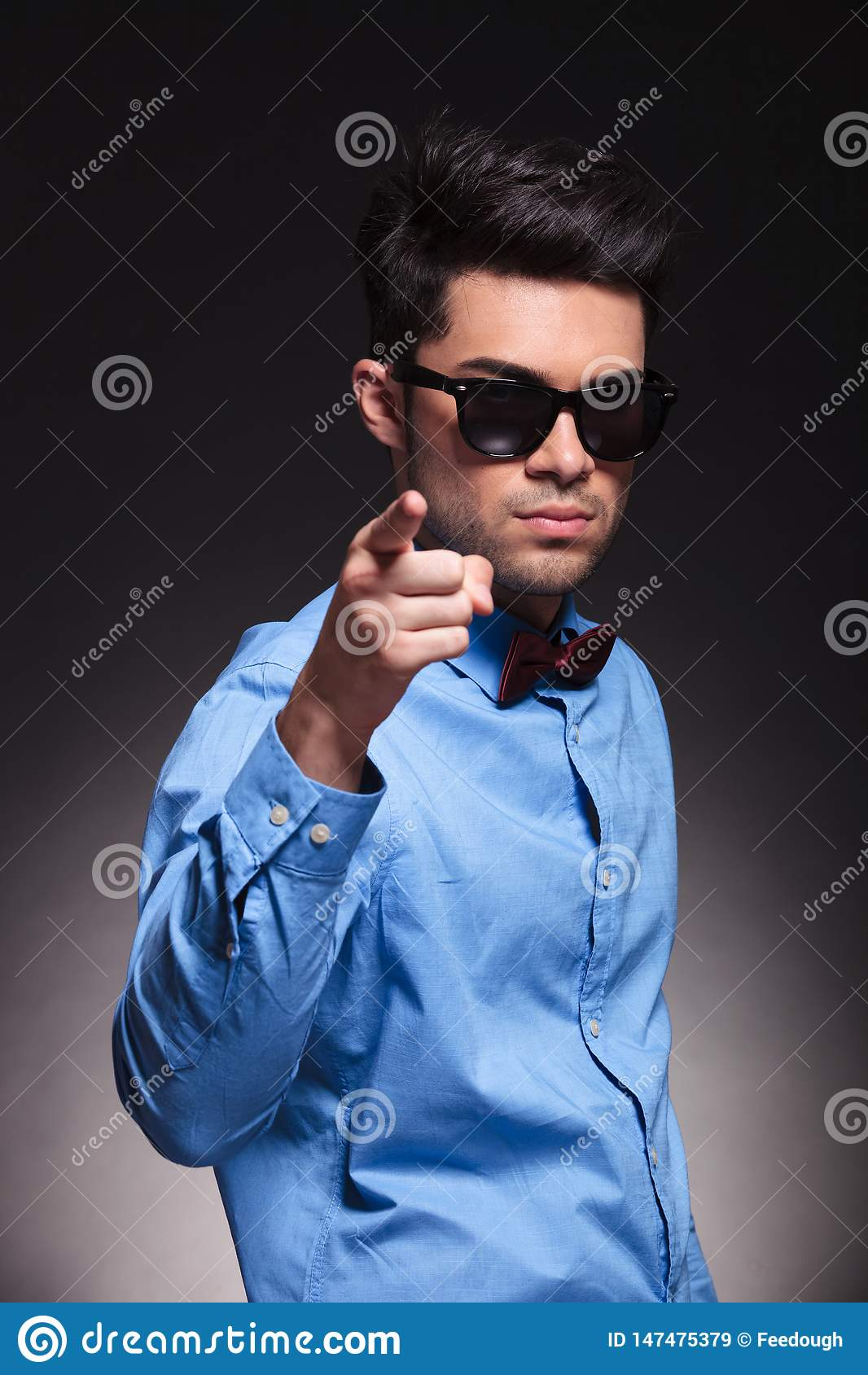 Ernster schauender junger Mann, der auf die Kamera zeigt