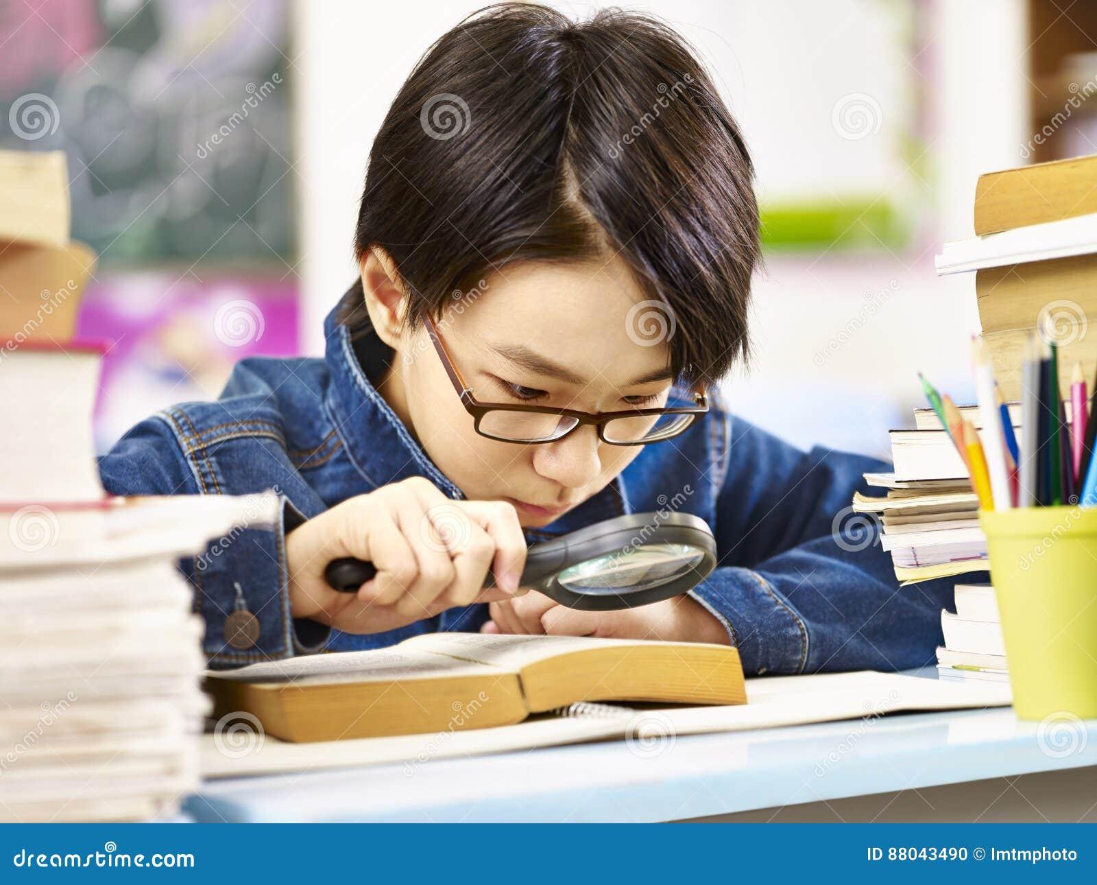 Ernster und neugieriger asiatischer grundlegender Schüler