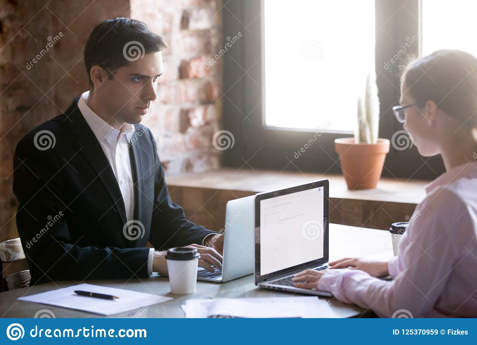 Ernstig mannelijk en wijfje die elkaar bekijken die voor leiding worstelen