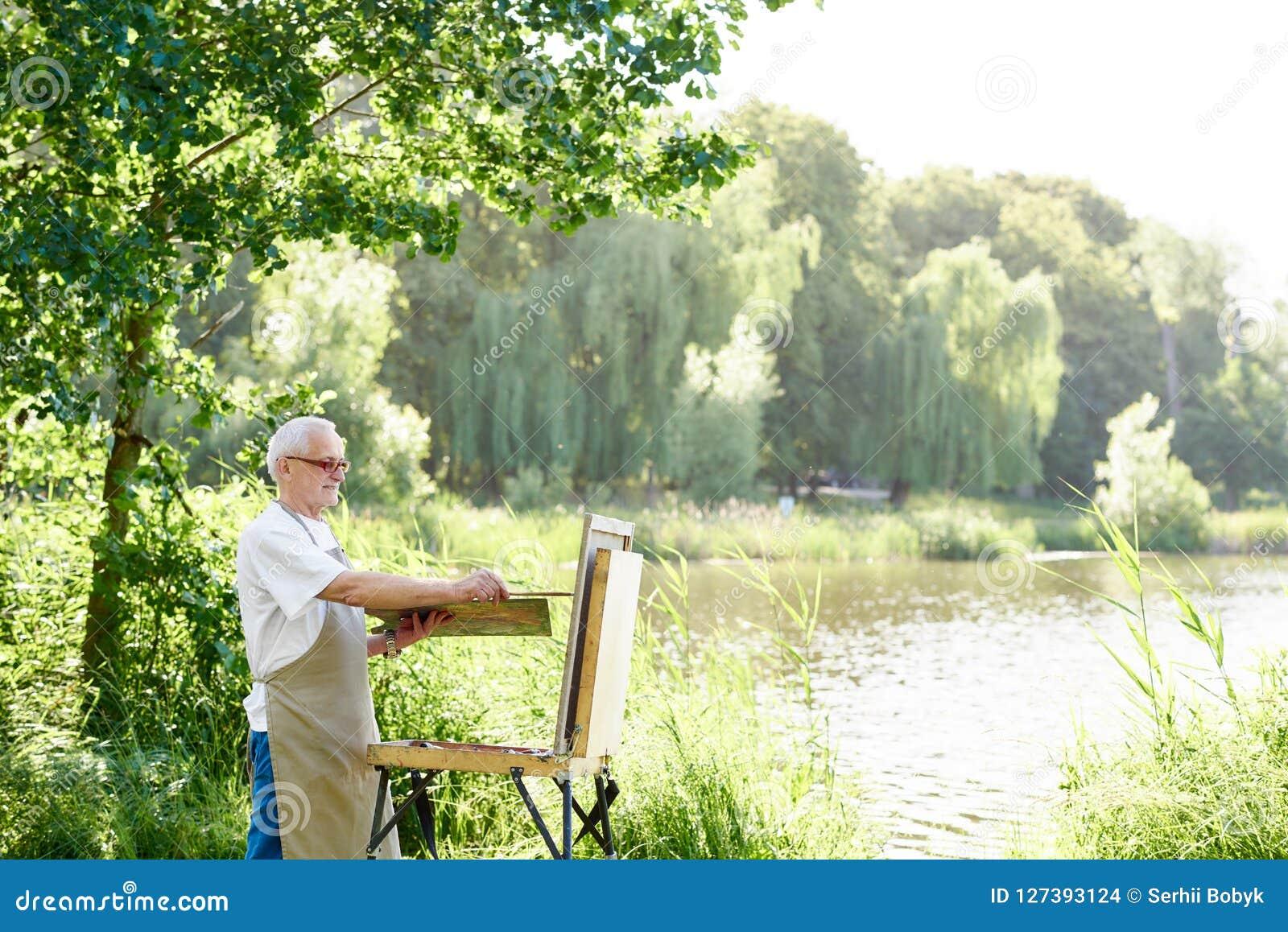 Ernstig mannelijk kunstenaarsholding borstel en het schilderen beeld op schildersezel op openlucht