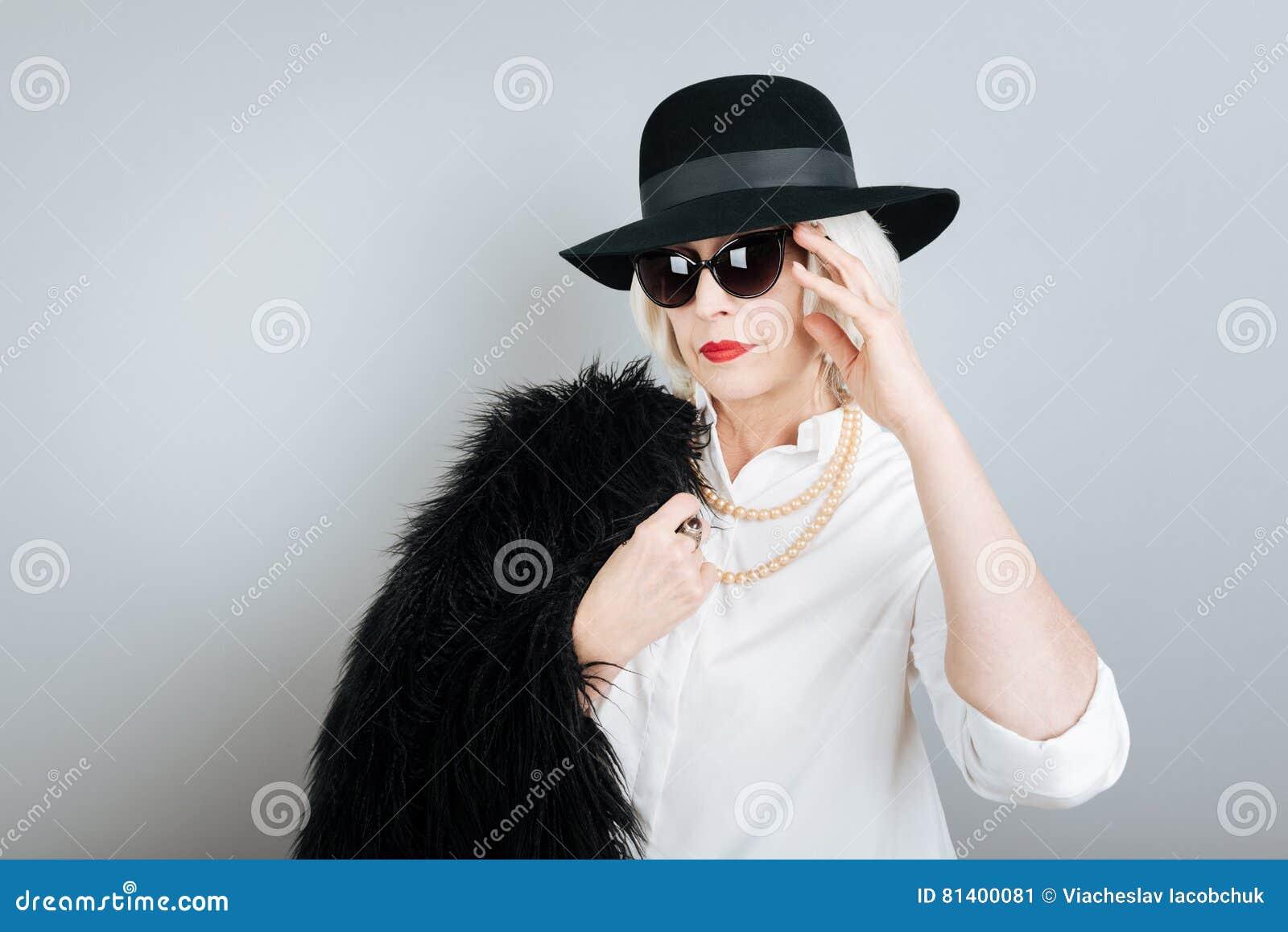 Ernstige hogere vrouw wat betreft zonglazen
