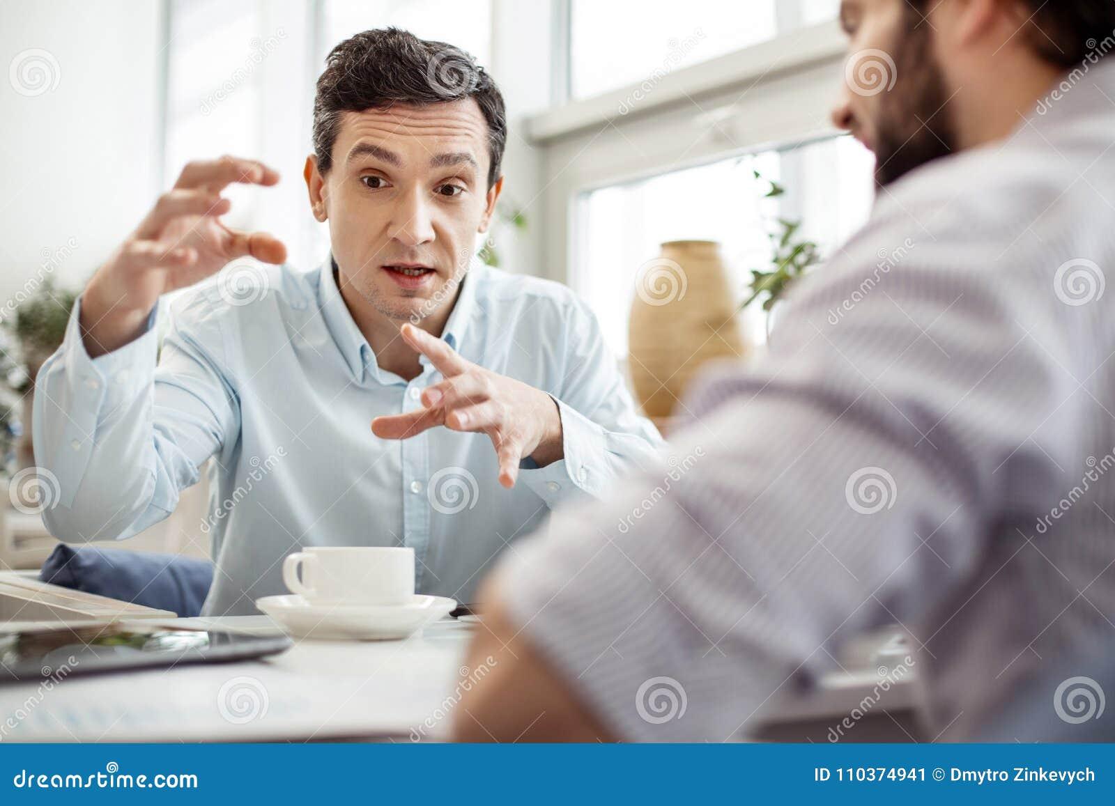 Ernstige jonge mens die het werk en het gesturing bespreken