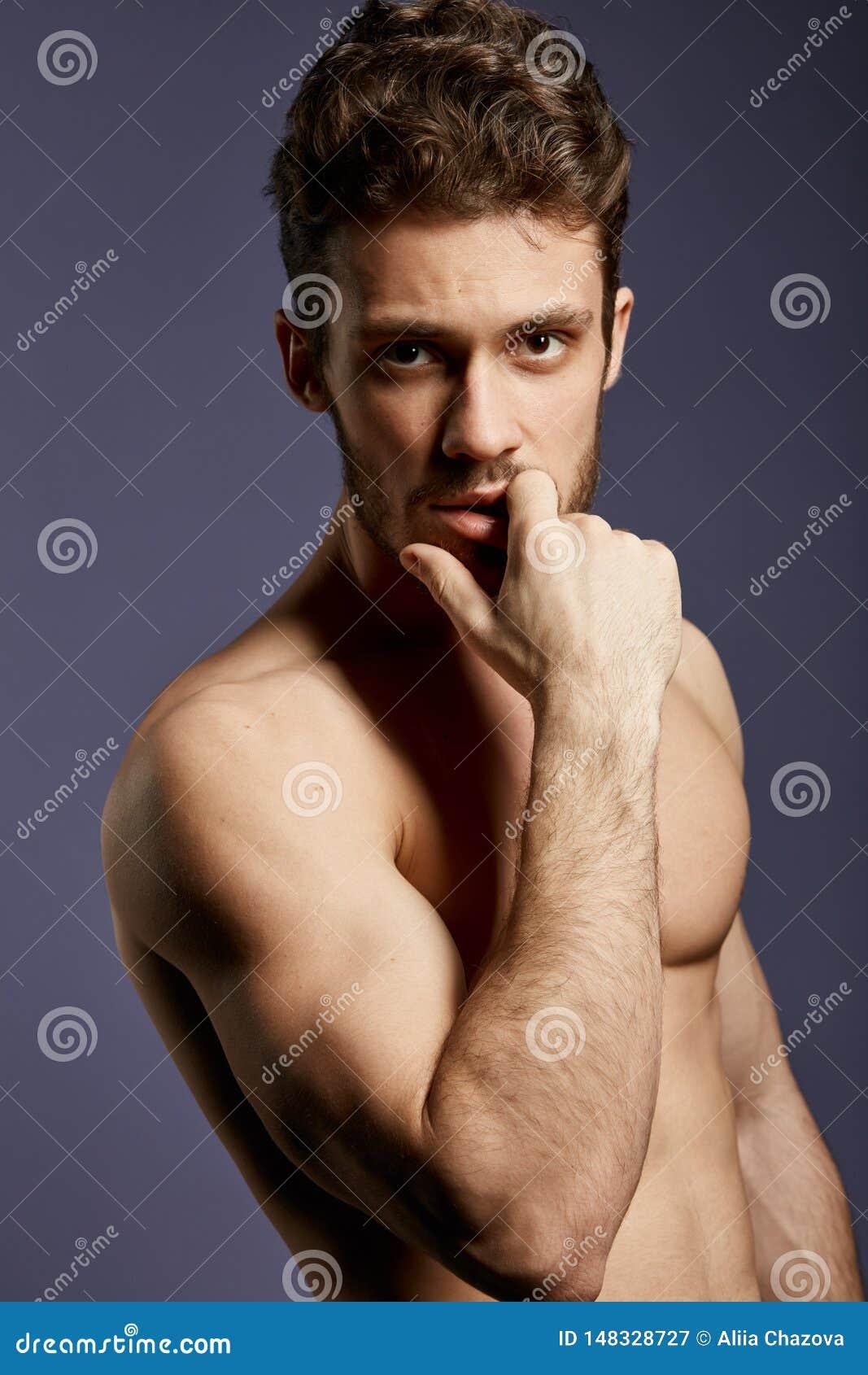 Ernstige ontzagwekkende mens met een vinger op zijn mond die de camera bekijken