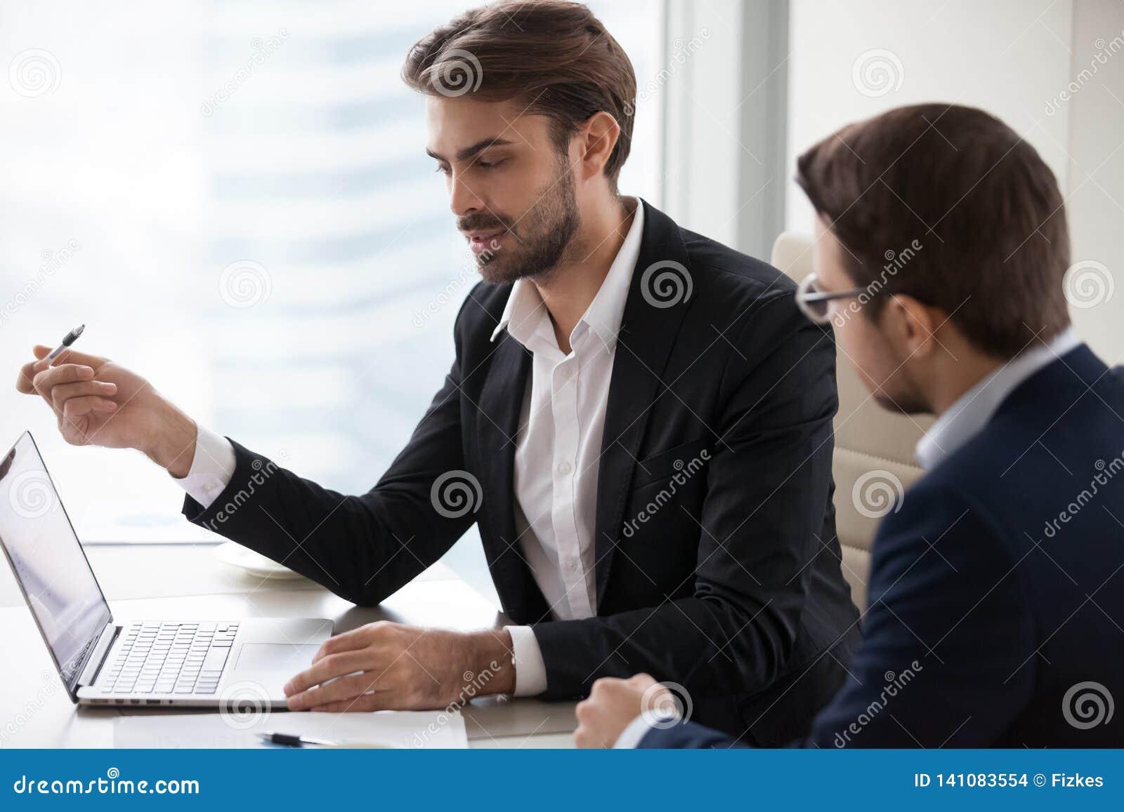 Ernstige zakenmanmanager die met cliënt het richten bij laptop spreken