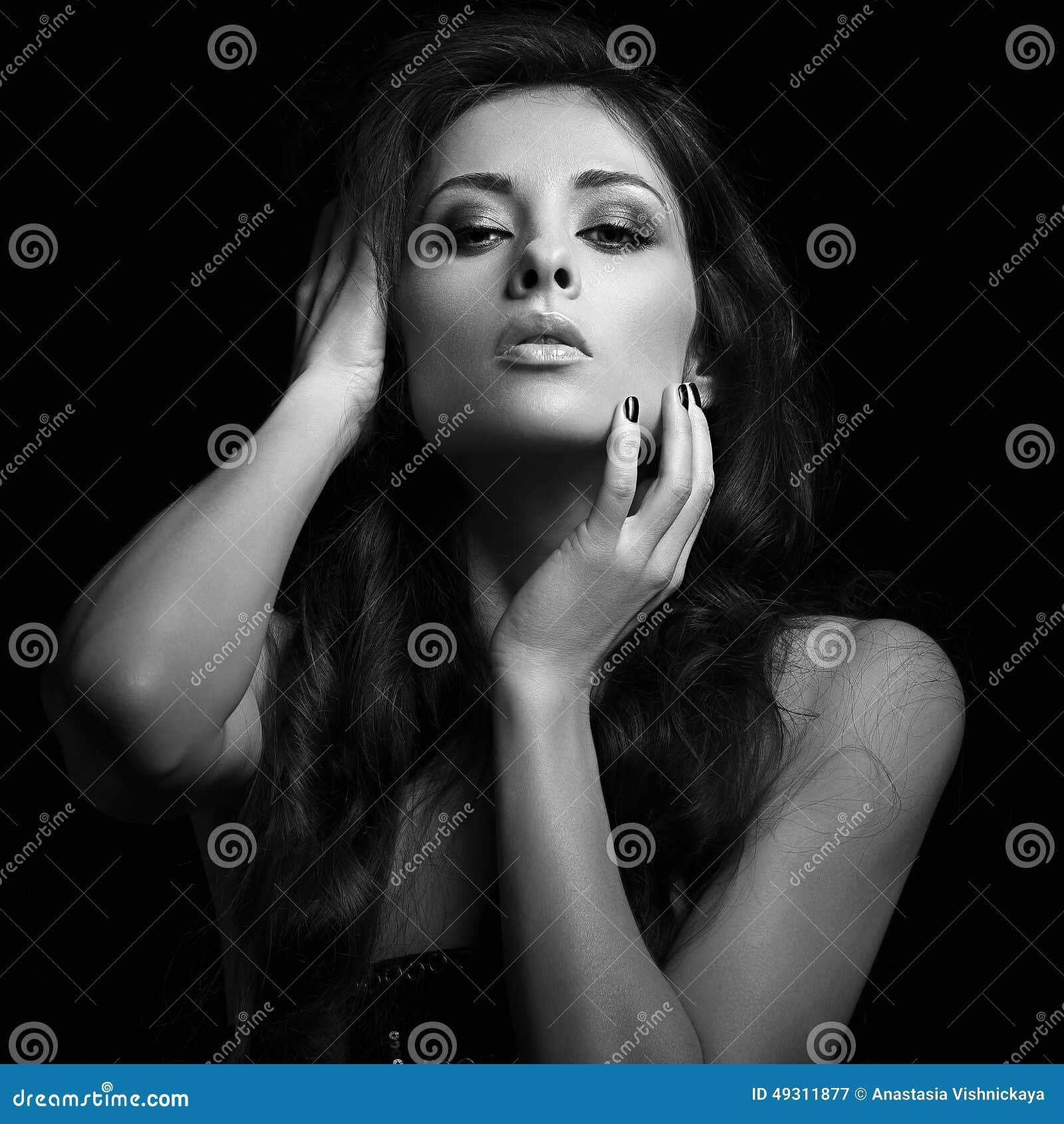 Erotische Frau, die mit dem langen braunen Haar heiß schaut