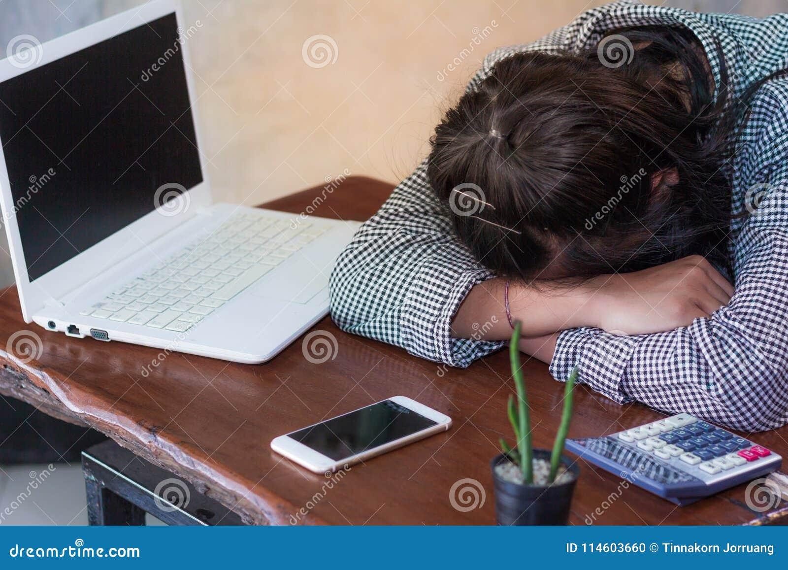 Erschöpfte Frauen, die am Arbeitsplatz nach hart arbeitend Tag schlafen