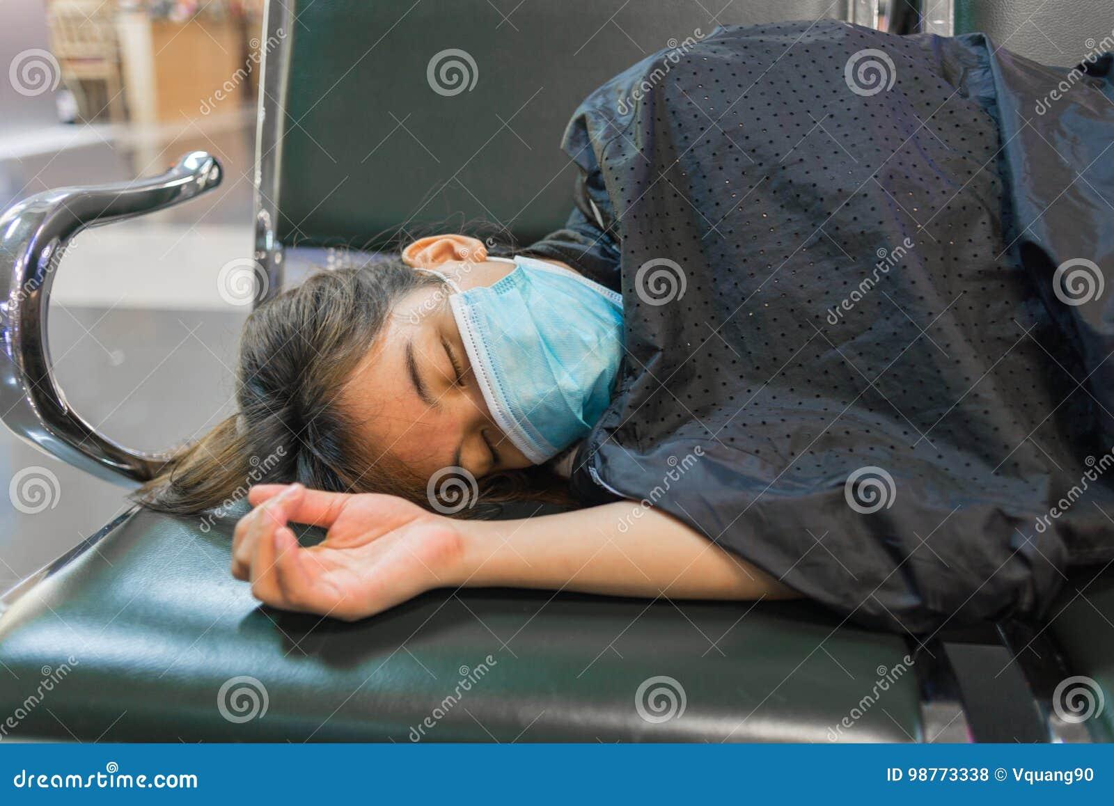 Erschöpftes Mädchen mit der Gazemaske, die auf der Bank liegt