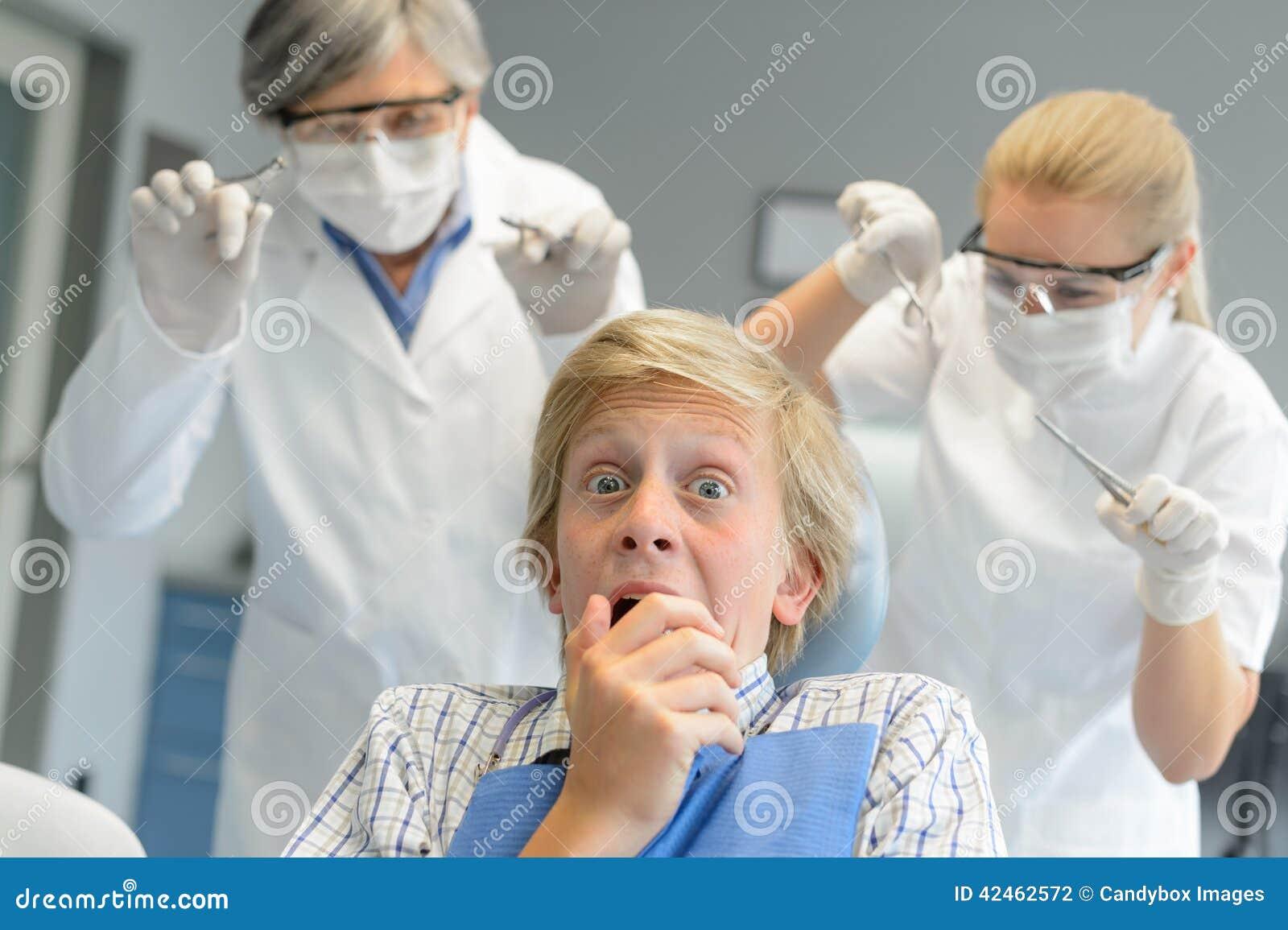 Erschrockener Jugendpatient erschrecken Zahnarzt und Krankenschwester