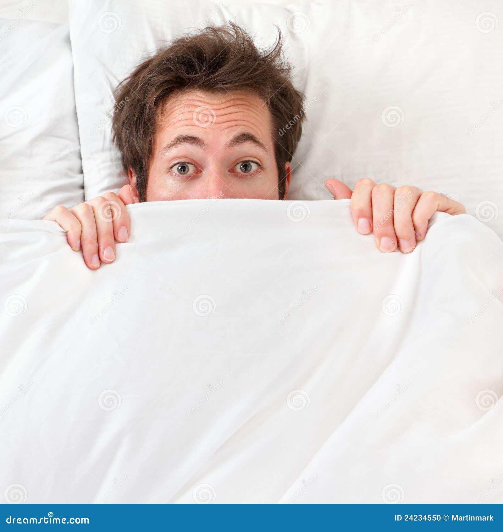 erschrockener mann der im bett sich versteckt stockfoto bild von bedtime wach 24234550. Black Bedroom Furniture Sets. Home Design Ideas