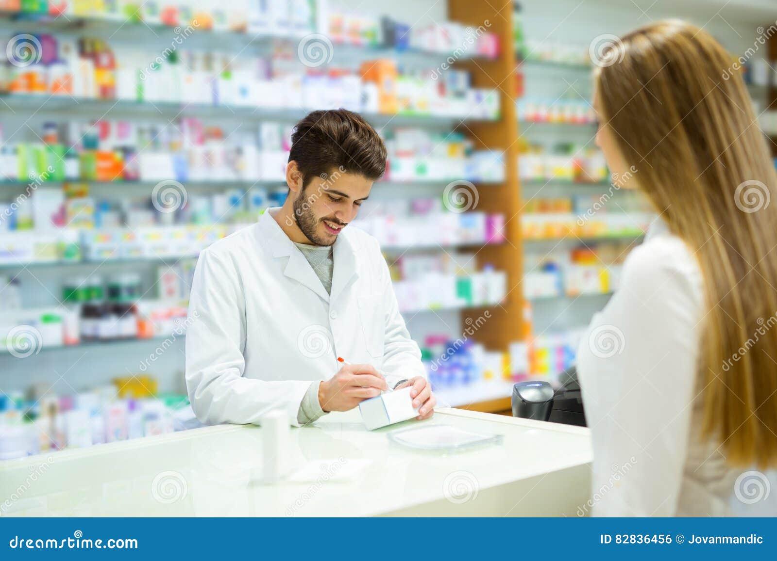Ervaren apotheker die vrouwelijke klant in apotheek adviseren