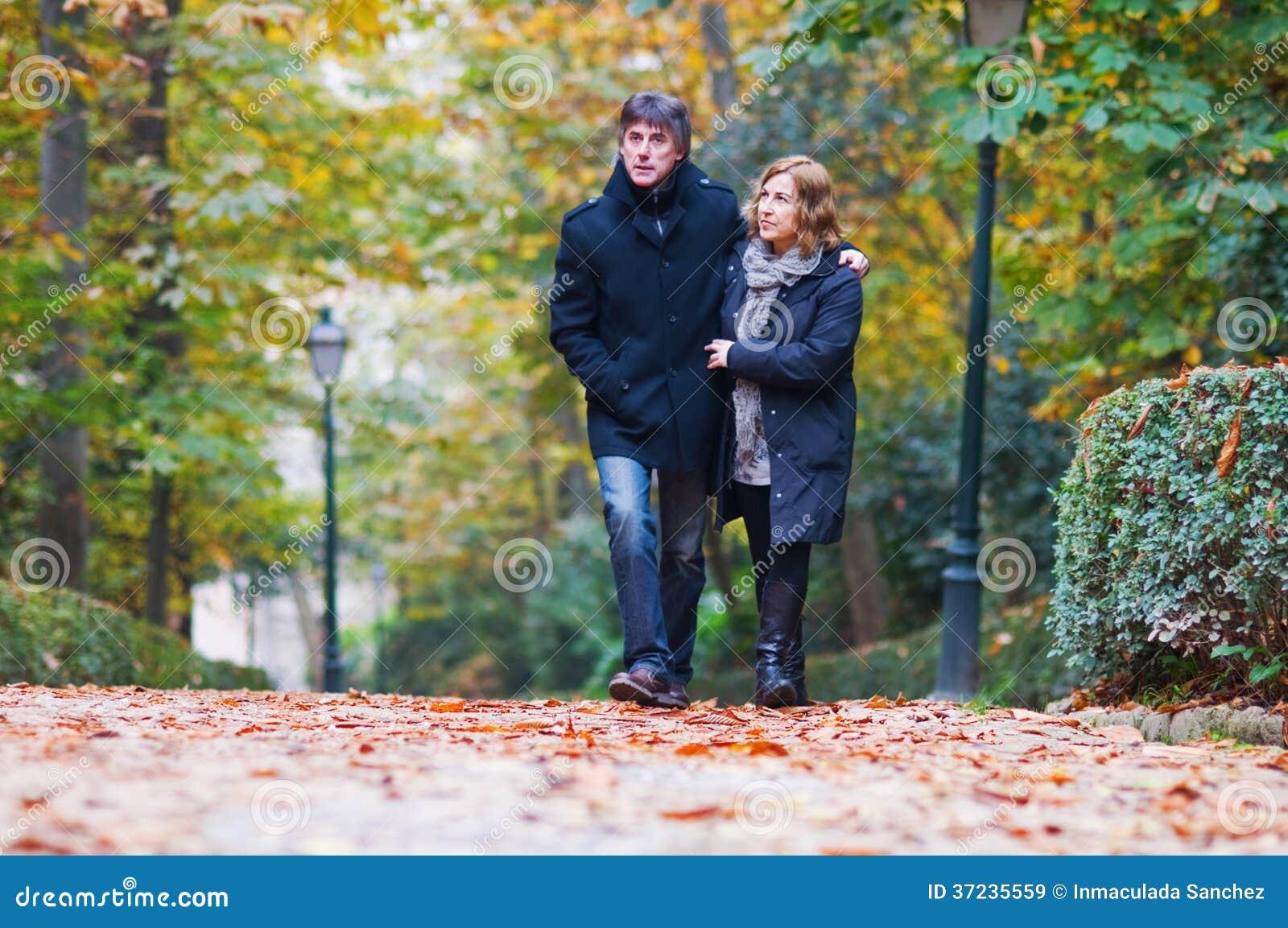 Erwachsene Paare in der Liebe, die in einen Park geht