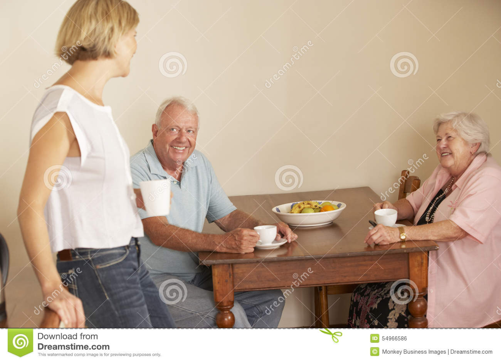 Erwachsene Tochter, die Tasse Tee mit älteren Eltern in der Küche teilt