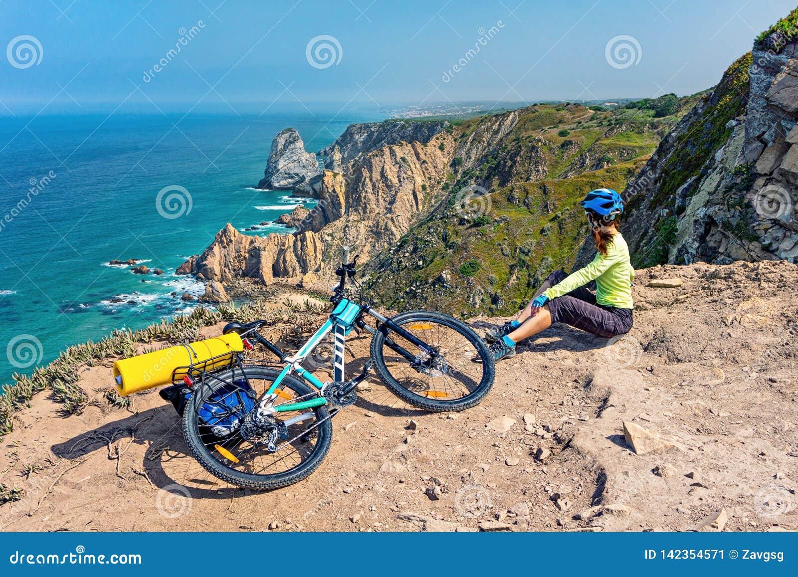 Erwachsener attraktiver weiblicher Radfahrer mit ihrer Mountainbike sitzt auf einer felsigen Küste des Ozeans