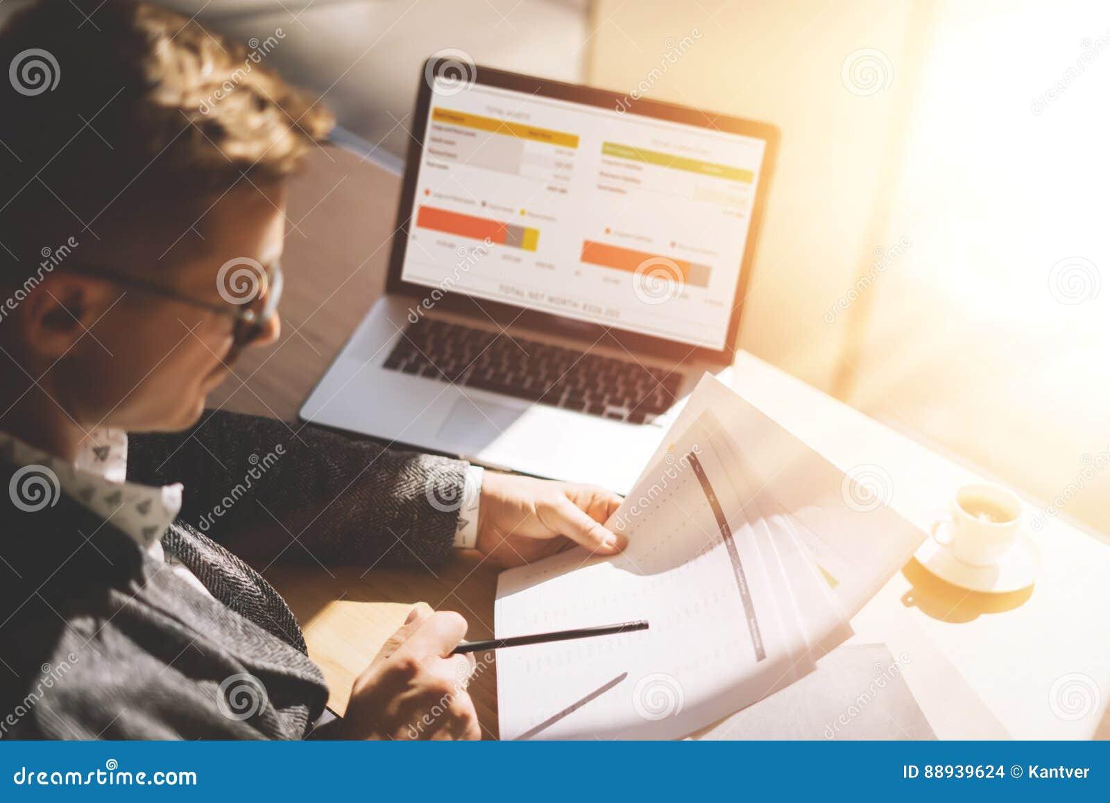 Erwachsener Geschäftsmann in den Brillen, die im sonnigen Büro auf Laptop beim Sitzen am Holztisch arbeiten Mann analysieren Doku