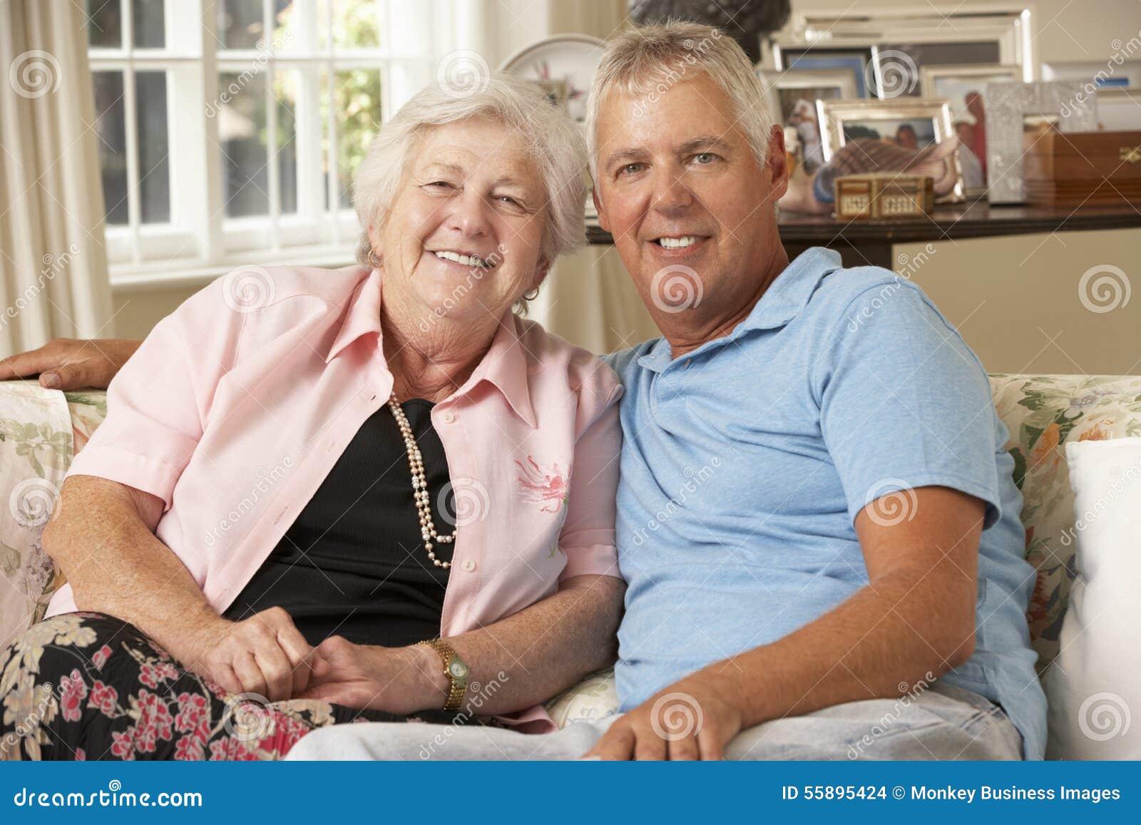 Erwachsener Sohn, der die ältere Mutter sitzt auf Sofa At Home Doing Crochet besucht