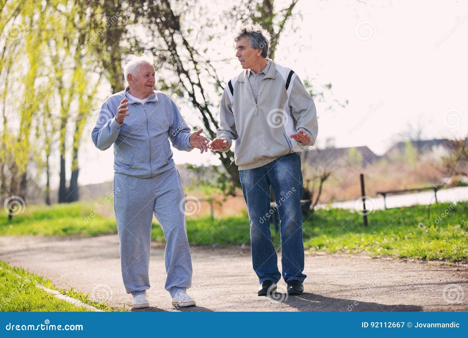 Erwachsener Sohn, der mit seinem älteren Vater geht