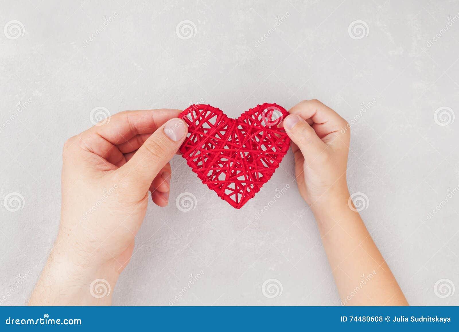 Erwachsener und Kind, die rotes Herz in den Händen von oben halten Familienbeziehungen, Gesundheitswesen, pädiatrisches Kardiolog