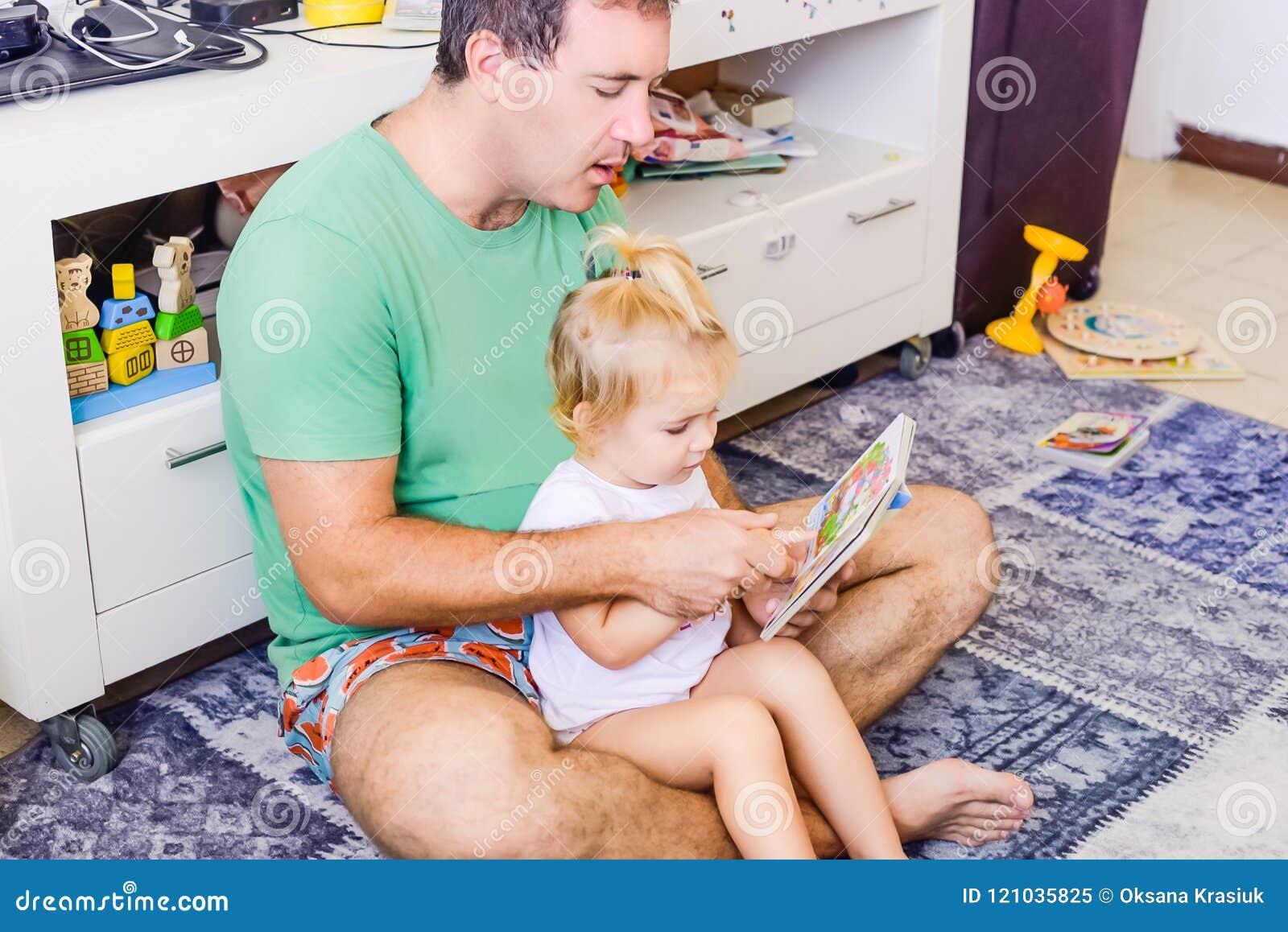 Erwachsener Vater mit dem Kleinkind, das zu Hause daughtersitting sind und Lesebuchgeschichte Kleines Mädchen, das auf Vaterschos