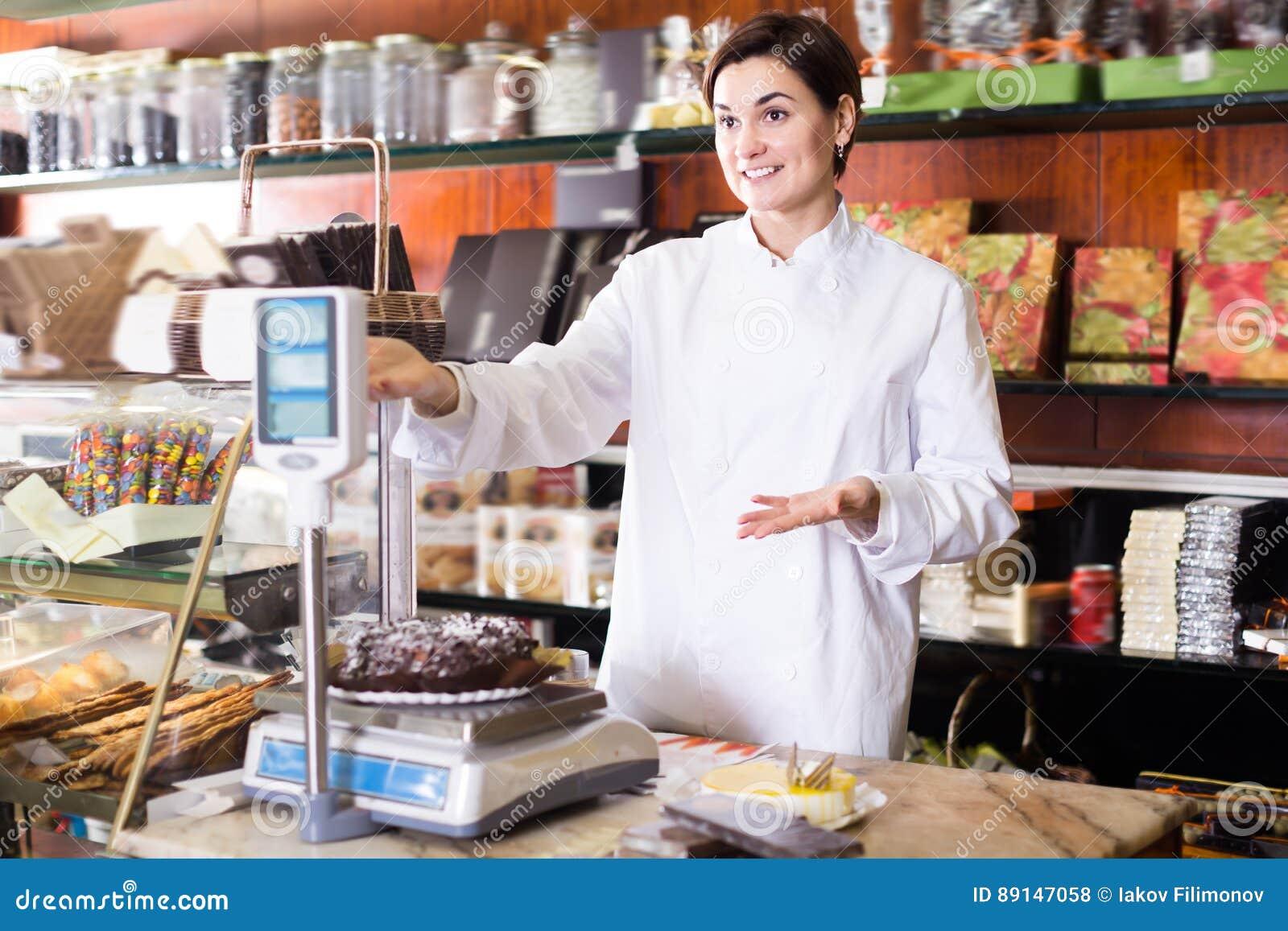 Erwachsener Verkäufer, der festlichen Schokoladenkuchen wiegt