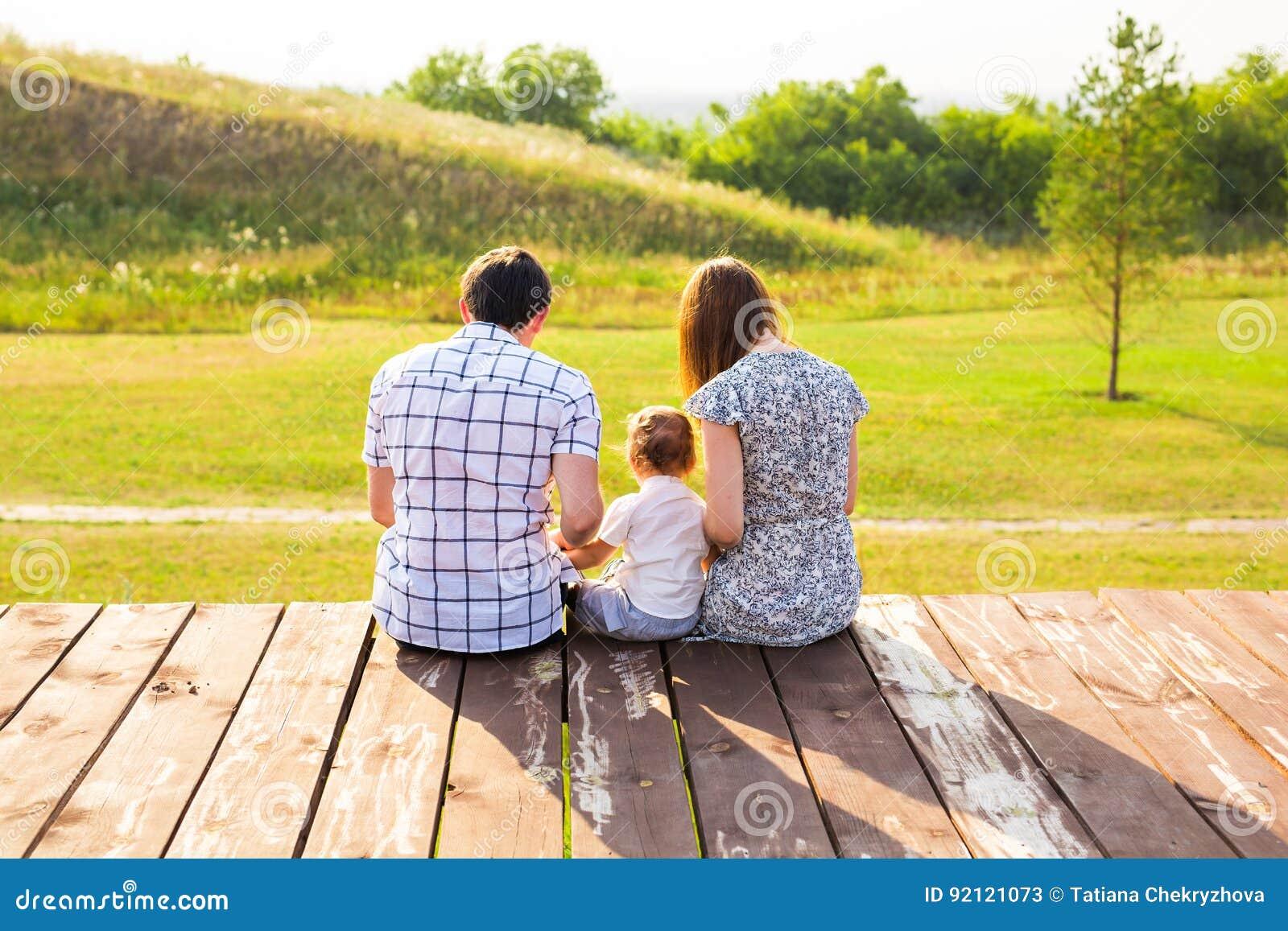 Es gibt 3 Mädchen und ihre Mutter, die auf der orange Couch sitzen Bild des glücklichen liebevollen Vaters, der Mutter und ihres