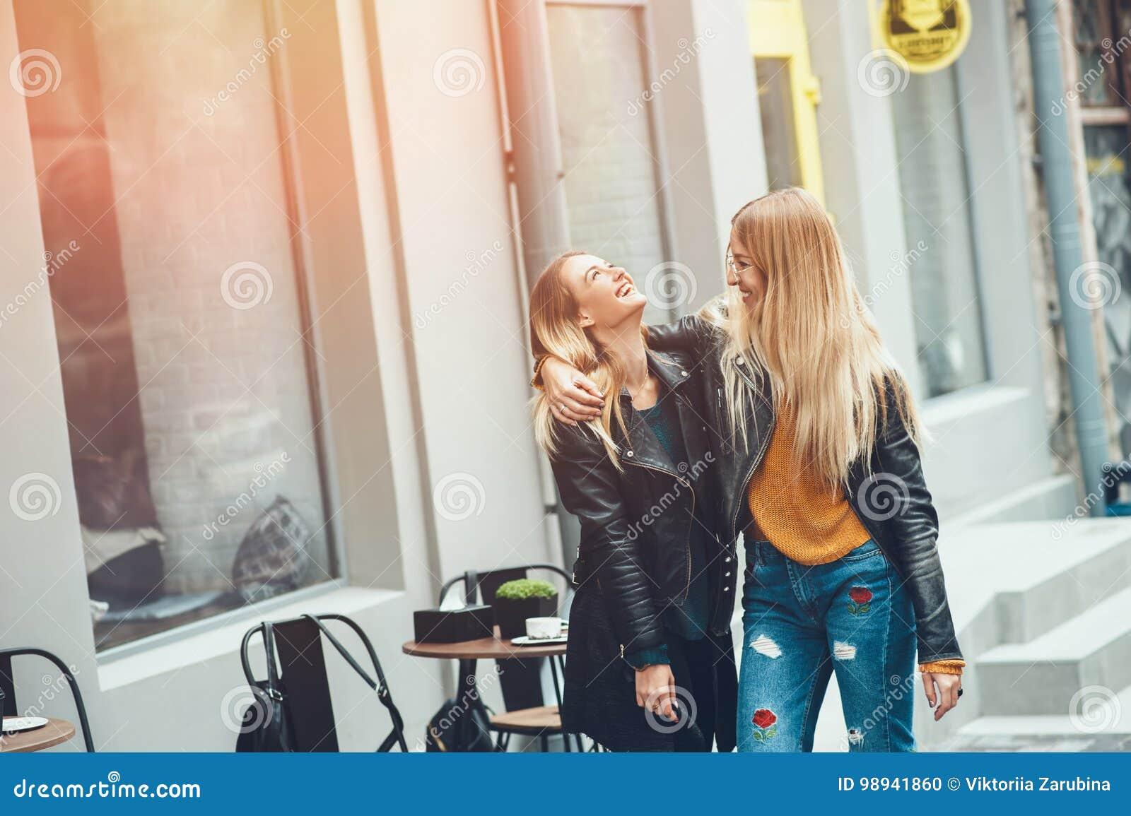 Es ist lustiger Weg mit bestem Freund! Gehendes Umarmen von zwei Schönheiten im Freien und Lachen auf Herbststraße