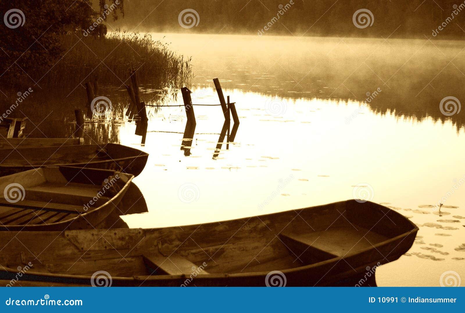Esboço do amanhecer pelo lago nevoento com barcos