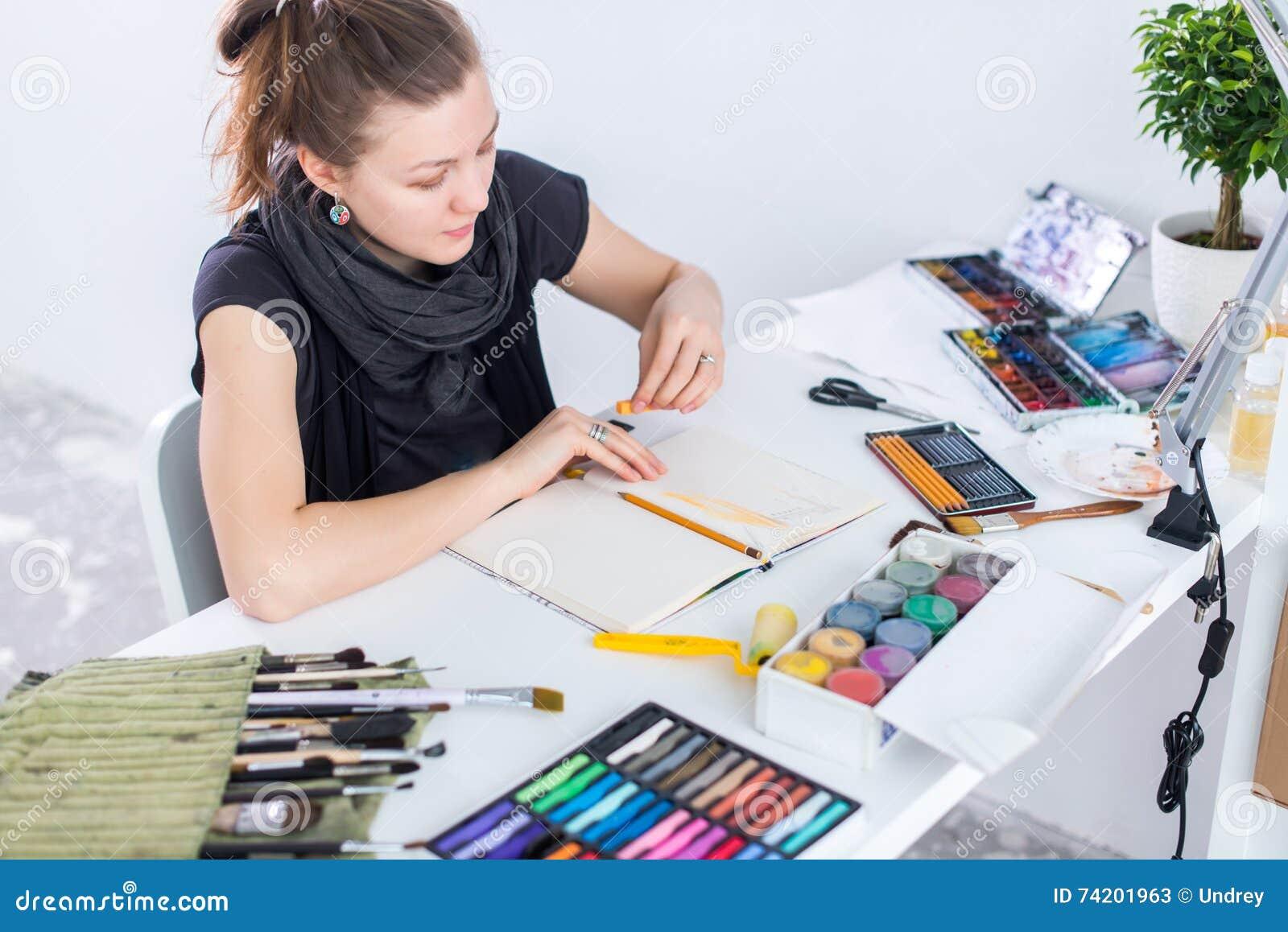 Esboço fêmea novo do desenho do artista usando o bloco de desenho com o lápis em seu local de trabalho no estúdio Retrato da vist