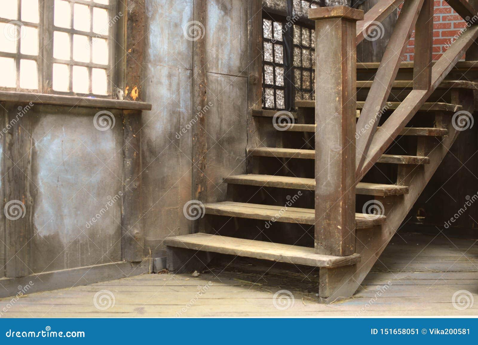 Escada empoeirada de madeira velha com um corrimão