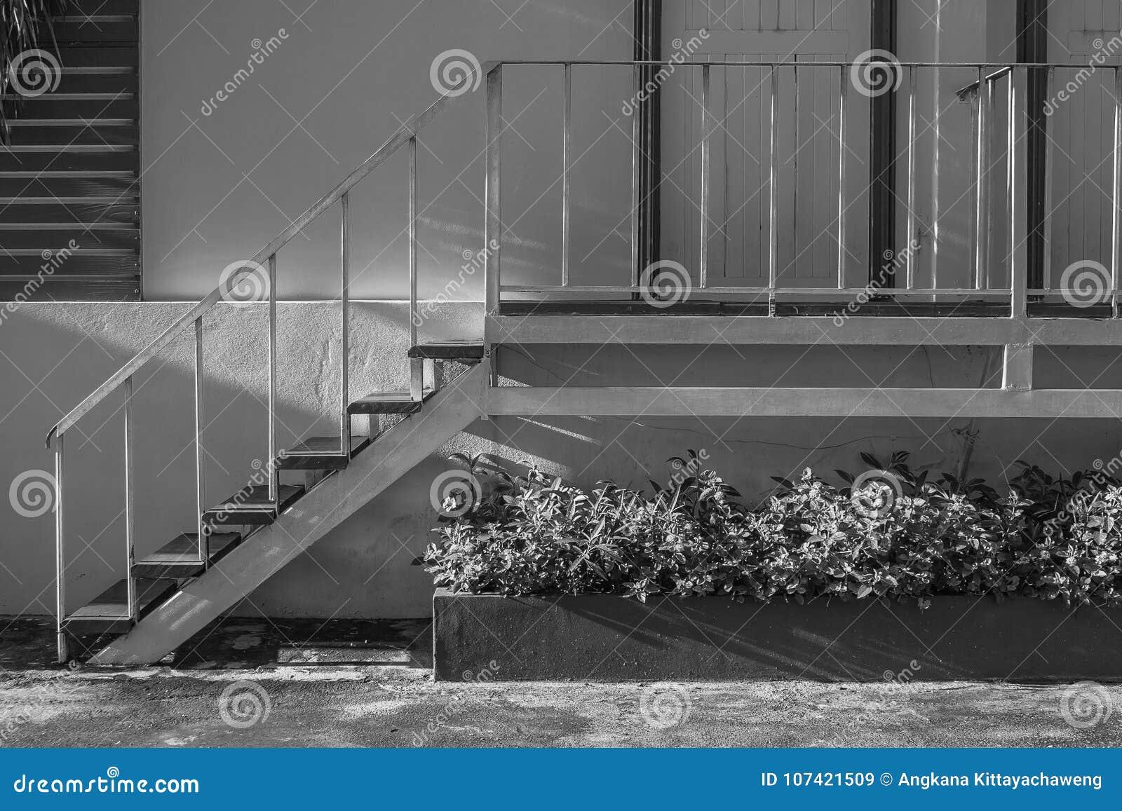 Escada pequena branca da vista lateral que vai acima à porta