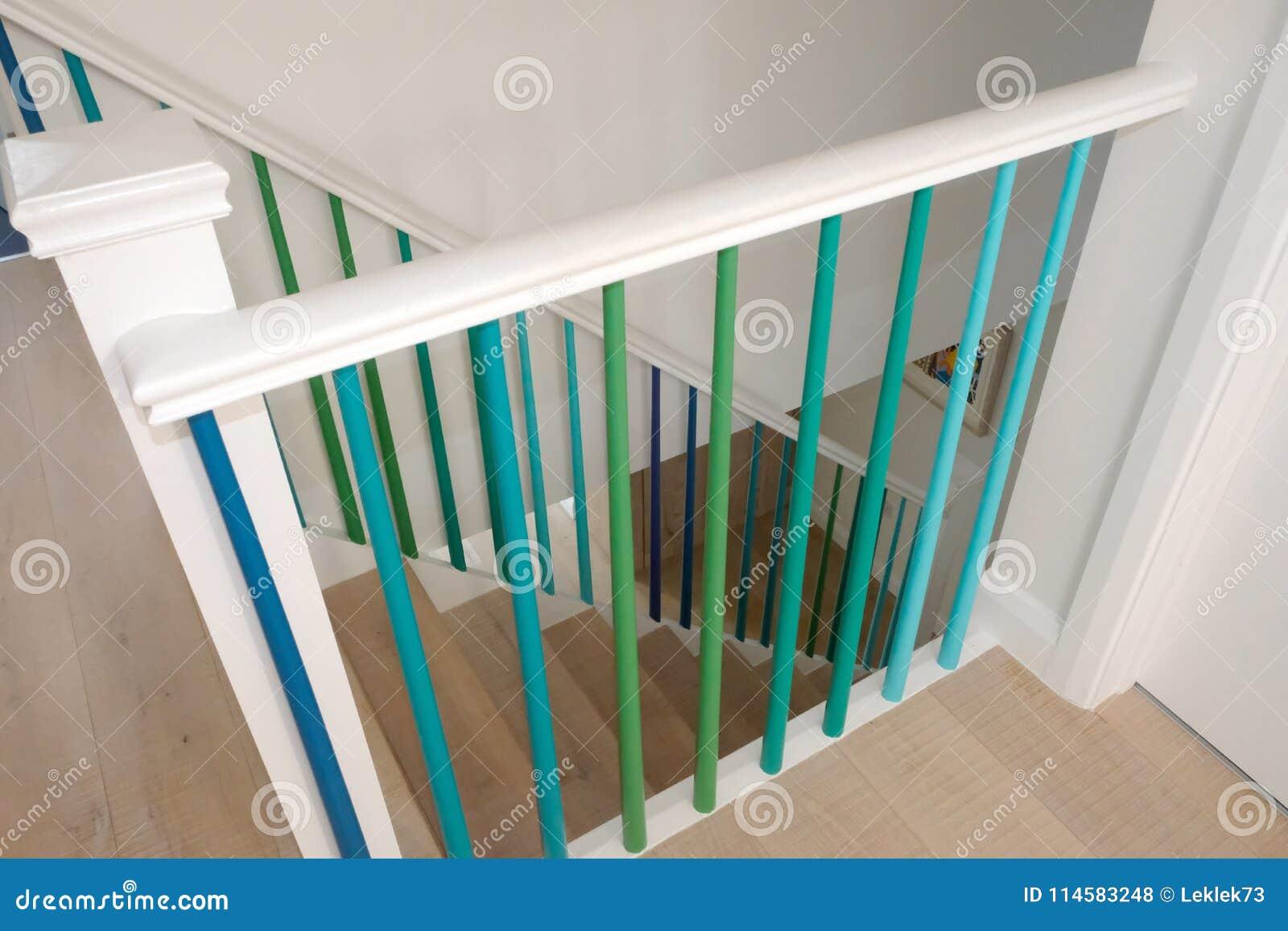 Escadaria de madeira minimalista com os eixos pintados no verde, na turquesa e em cores azuis do ombre