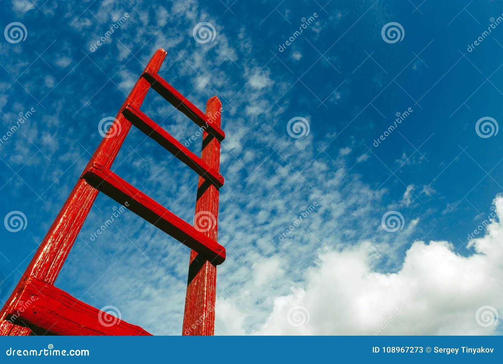 Escadaria de madeira vermelha contra o céu azul Conceito do crescimento do céu da carreira do negócio da motivação do desenvolvim