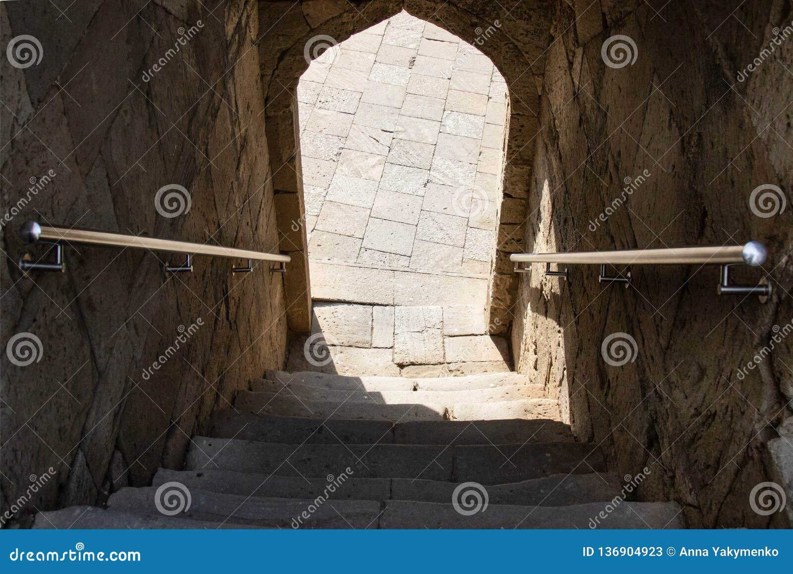 Escadas abaixo da entrada através do arco, sombra, etapas