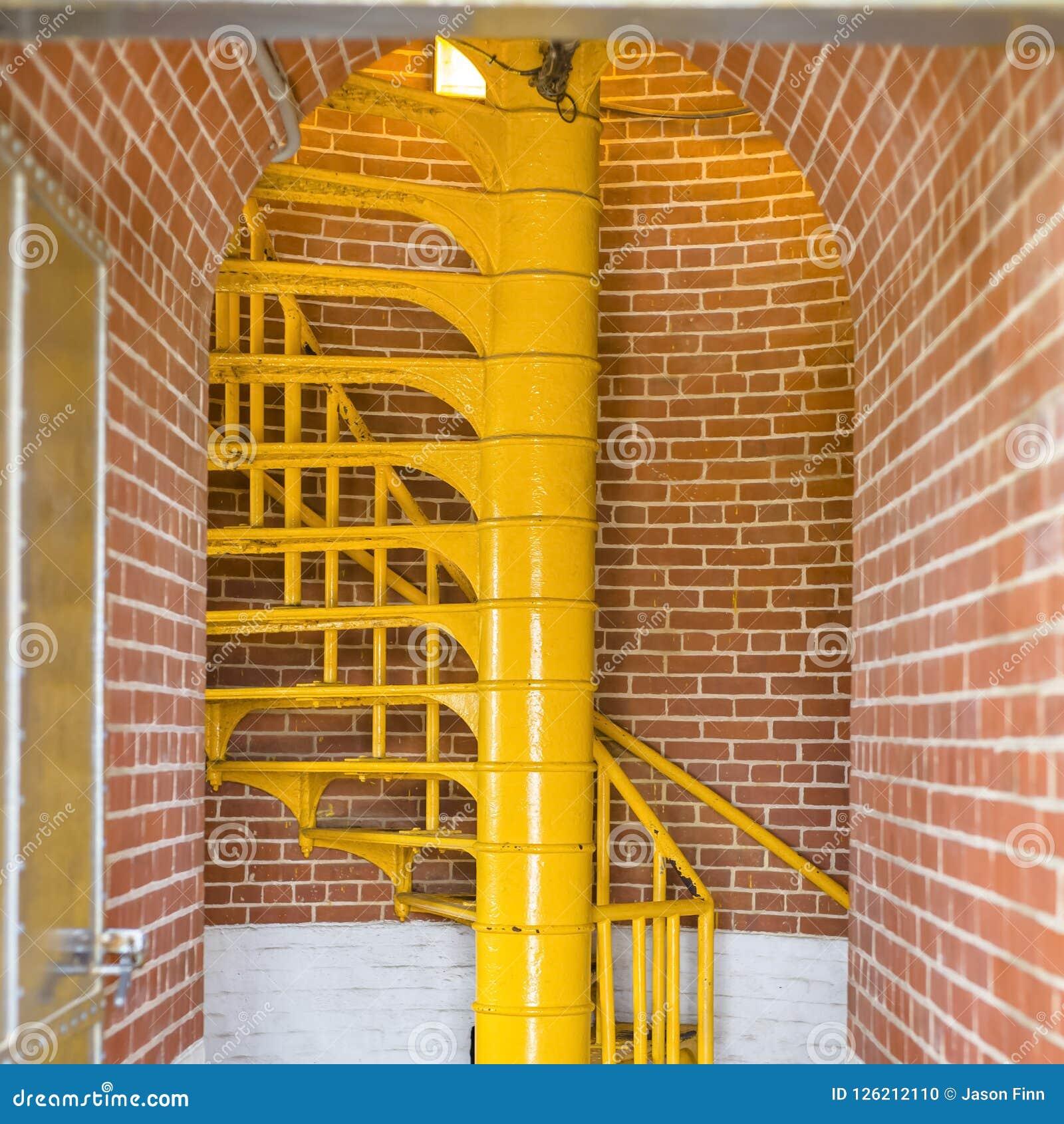 Escadas amarelas e maneira arqueada da entrada de farol