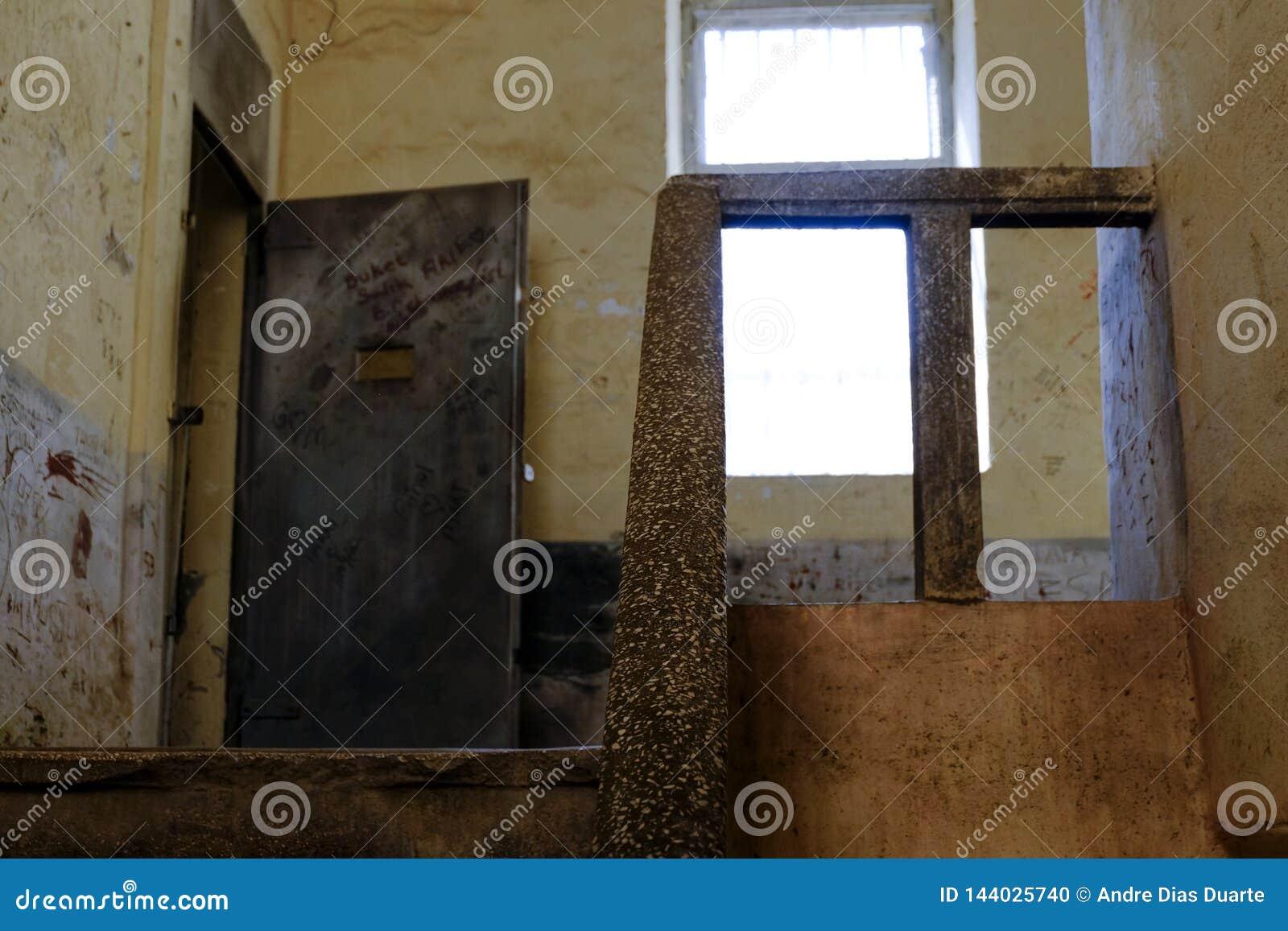 Escadas da pedra da prisão e porta do metal