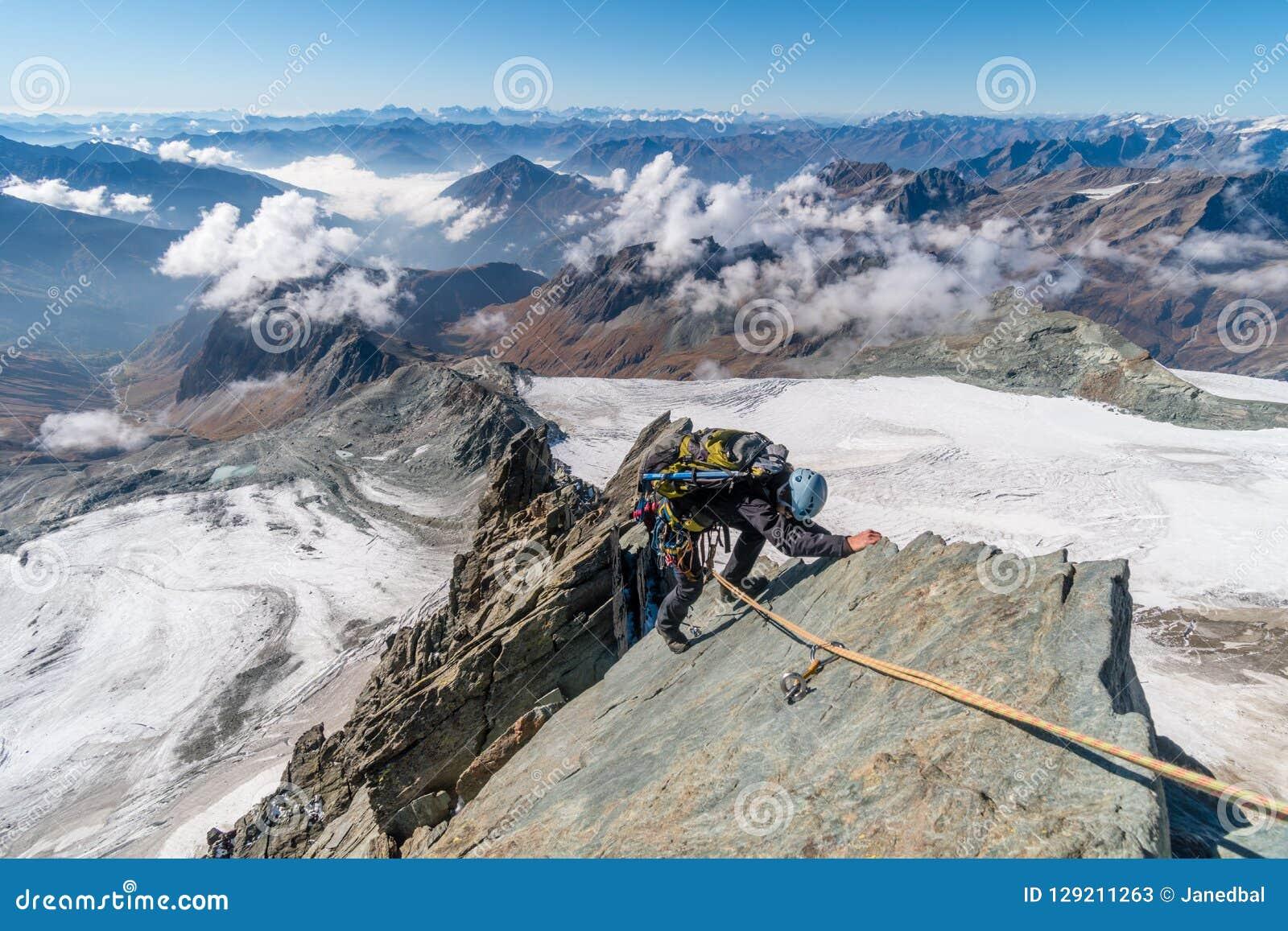 Escalador de roca en el canto en Grossglockner, la montaña más alta de Studlgrat en Austria