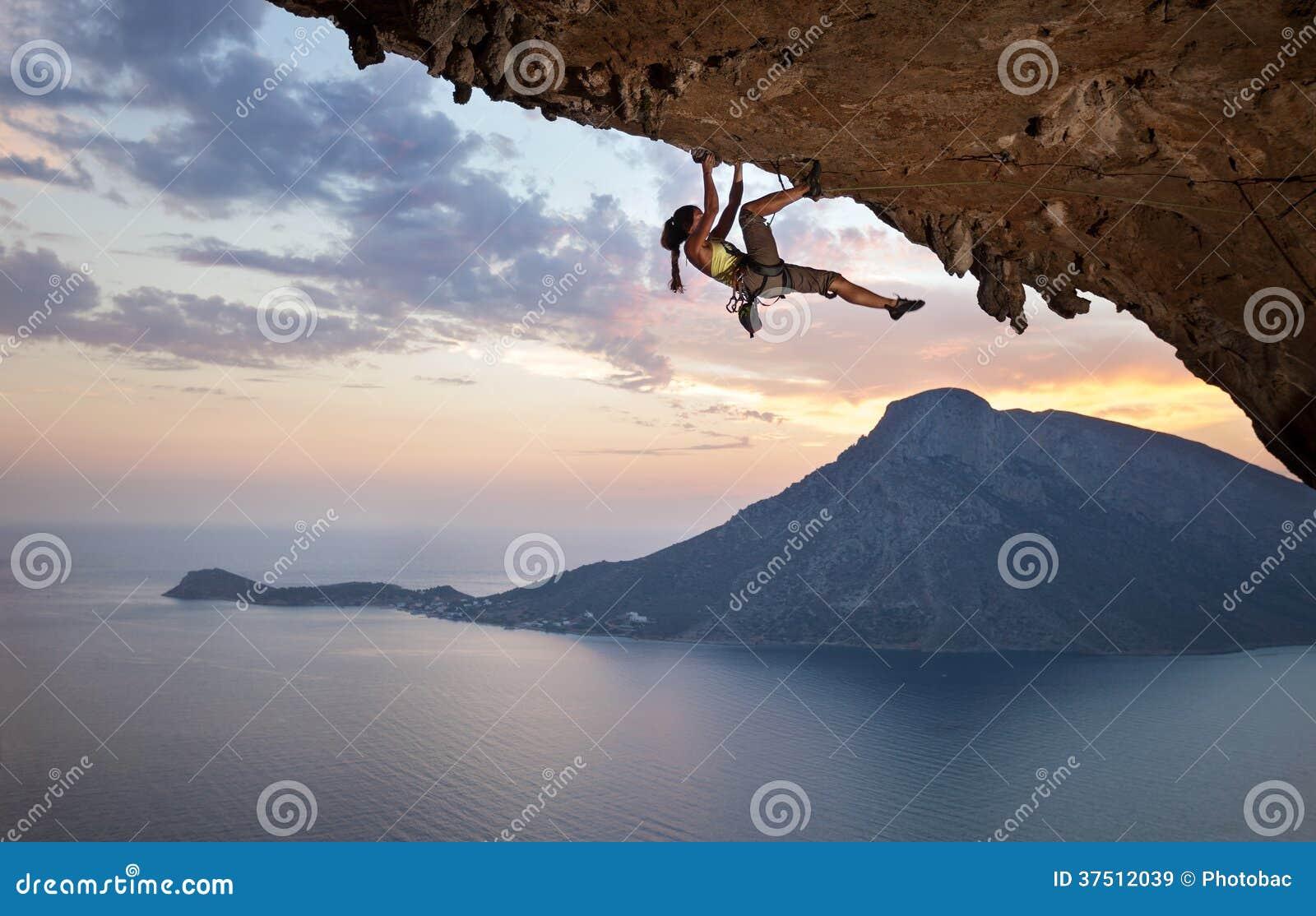 Escalador de roca femenino joven en la puesta del sol
