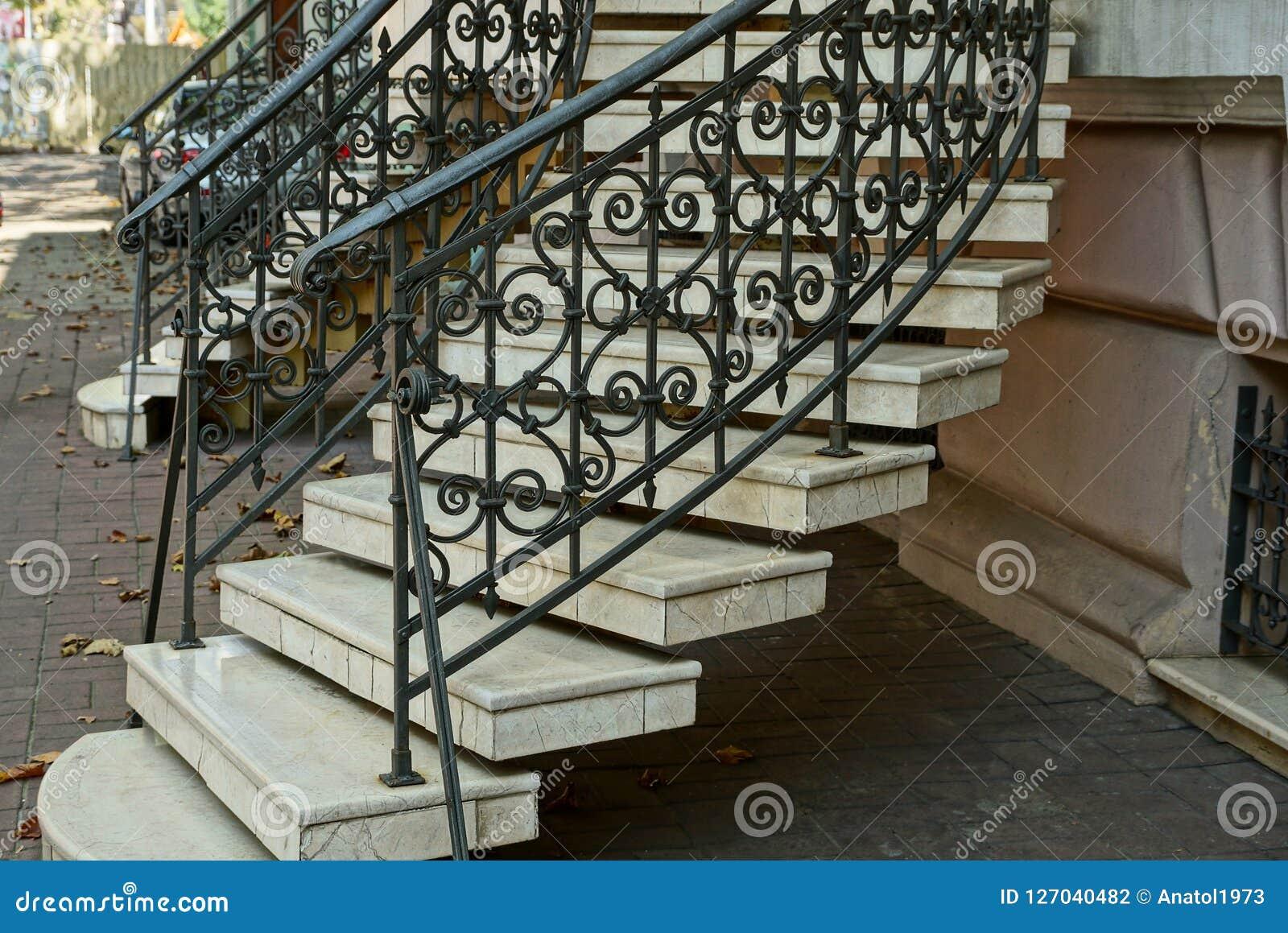 Escalera con pasos concretos grises y barandillas negras del hierro con un modelo forjado cerca de la pared en la acera