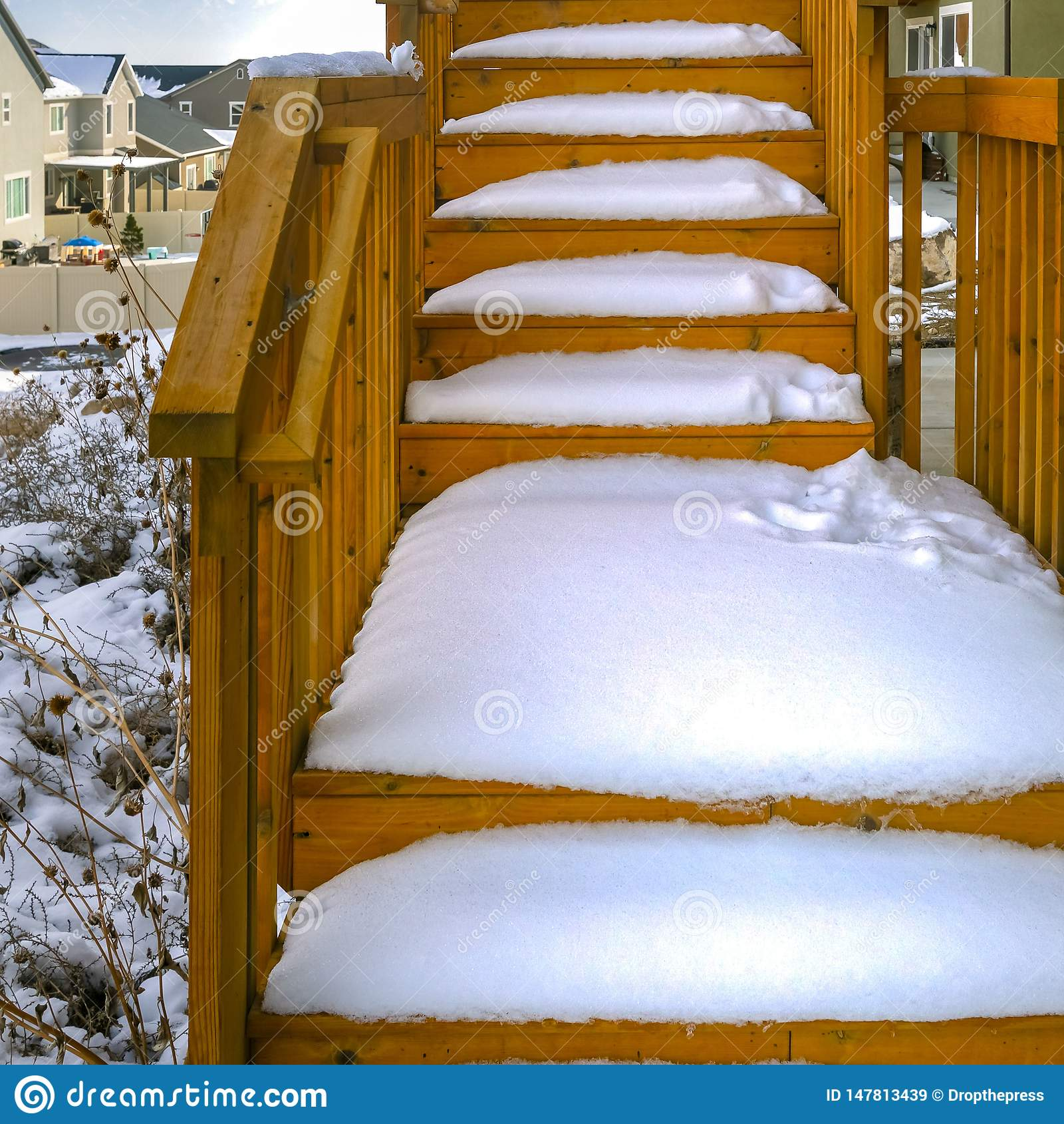 Escalera de madera al aire libre del cuadrado claro de un hogar cubierto con nieve durante la estación del invierno