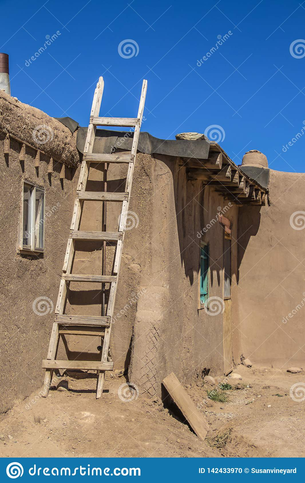 Escalera de madera hecha en casa contra el lado de la casa del pueblo del adobe del fango en donde el papel de alquitrán se está