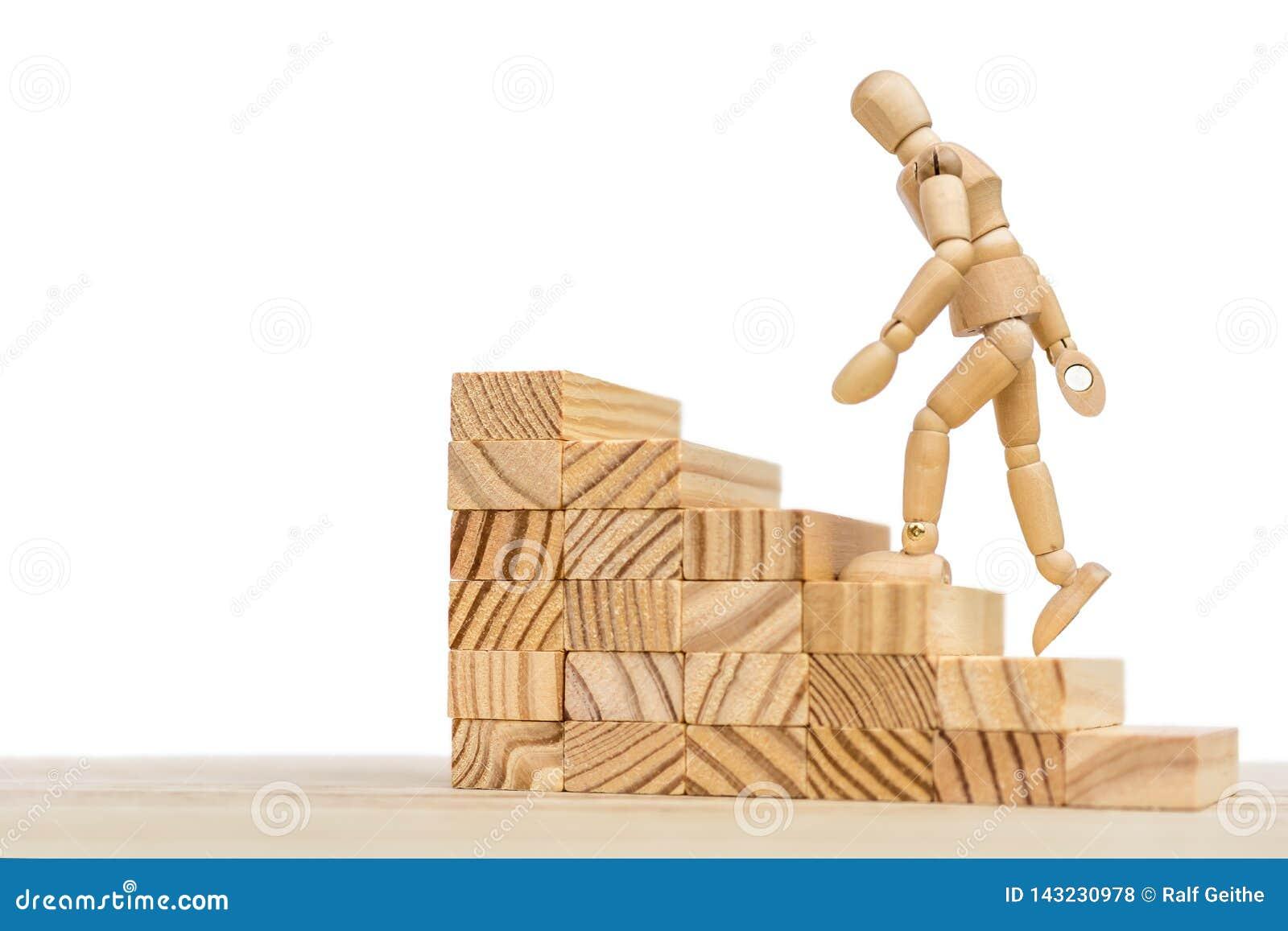 Escalera de madera y muñeca de madera contra el fondo blanco con el espacio libre para más lejos corregir