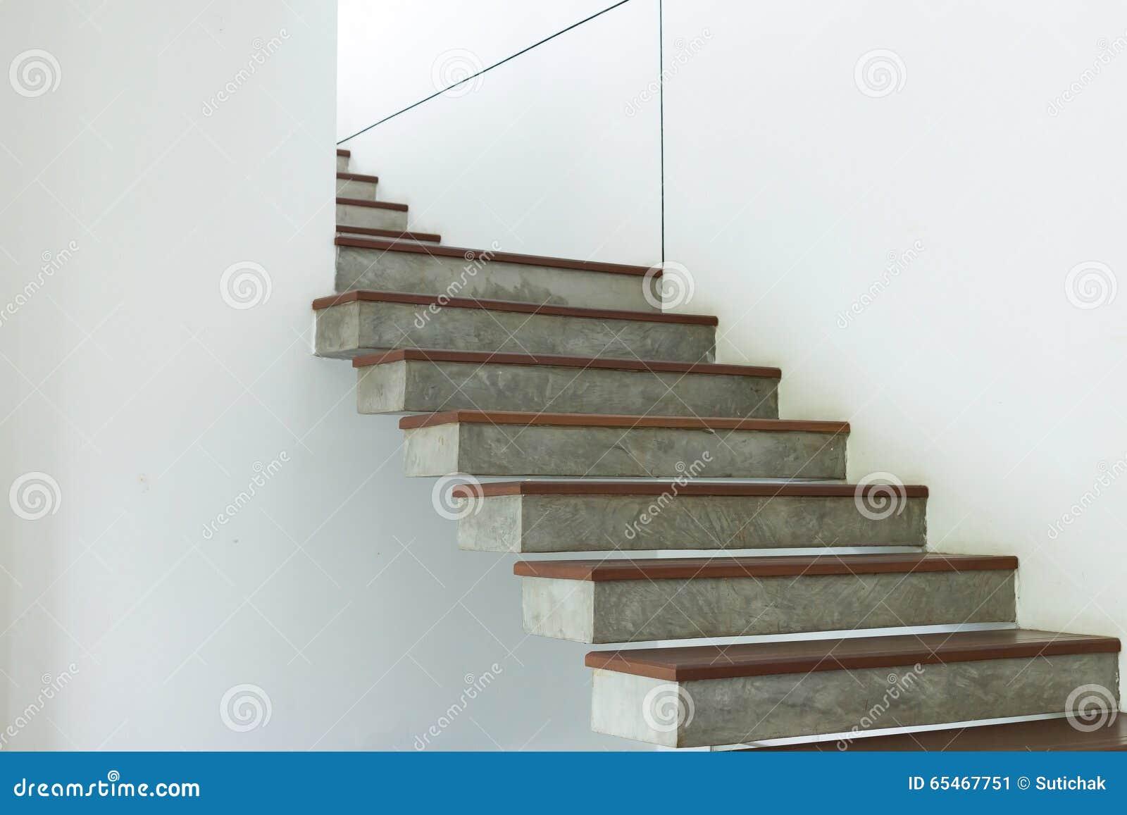escalera del cemento y de madera en la pared blanca del