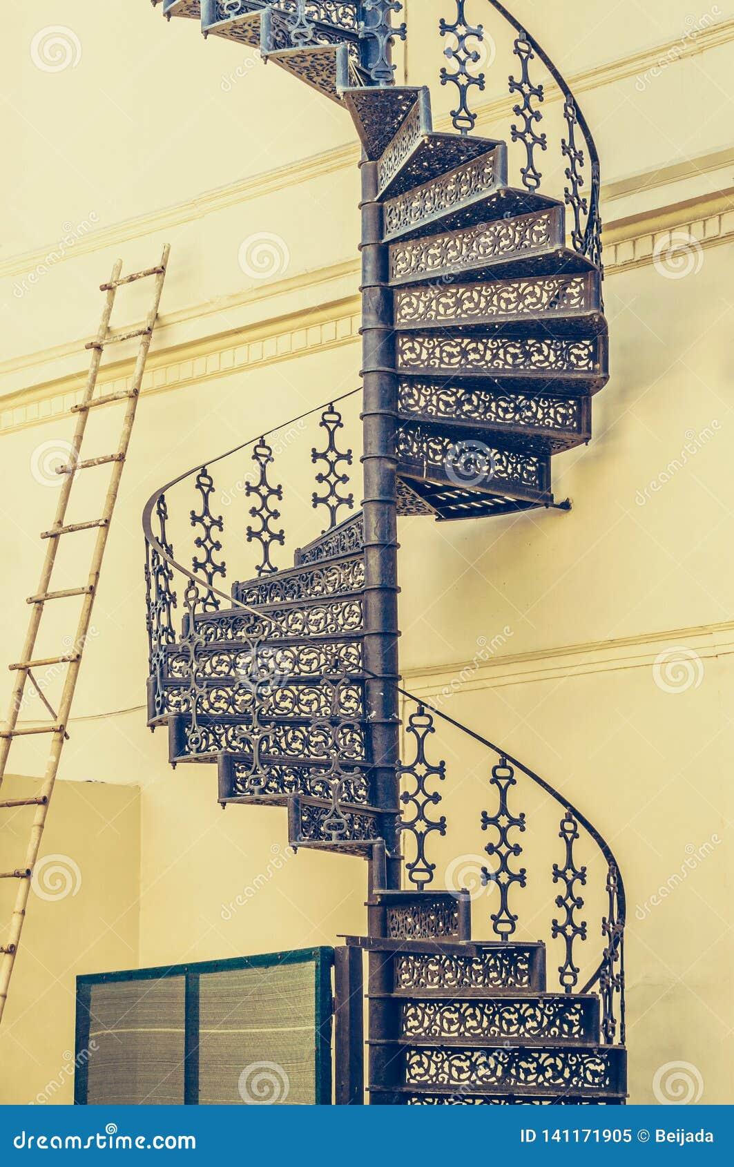 Escalera espiral labrada del escalera del vintage y de bambú en la pared