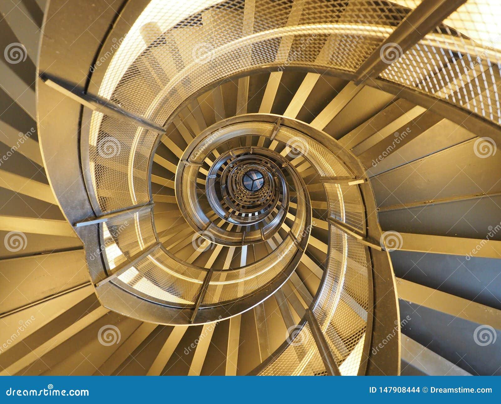 Escalera espiral moderna, de oro que da una visión hipnótica