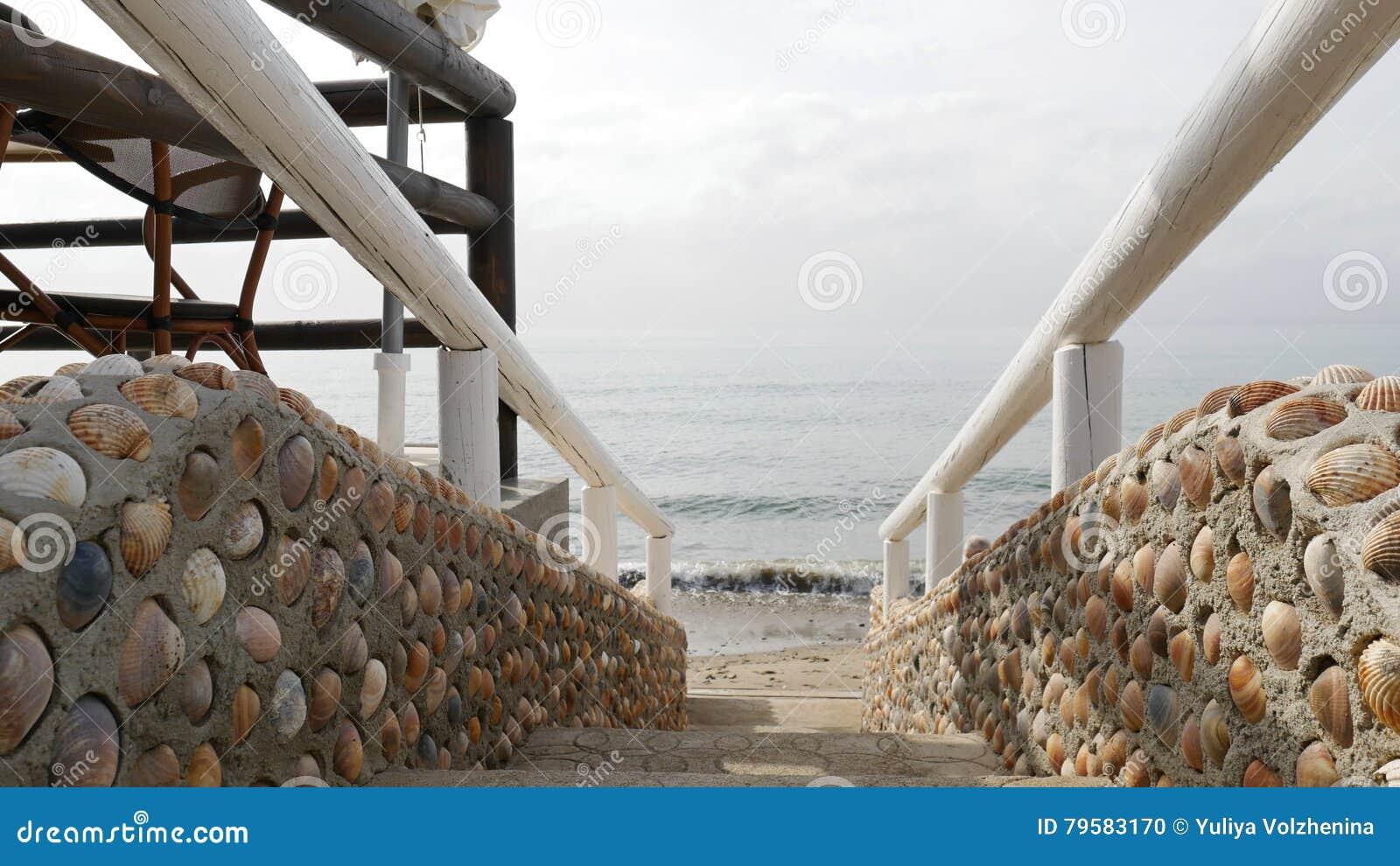 Escaleras hechas de las cáscaras y de la barandilla de madera que llevan al mar