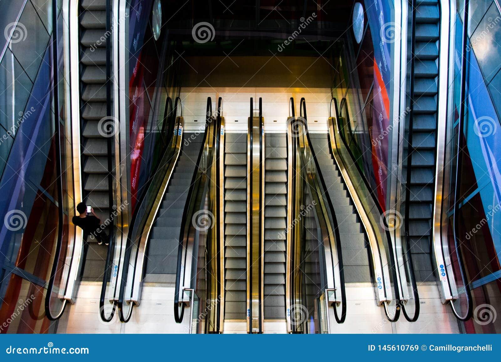 Escaleras móviles iluminadas y coloreadas en una alameda