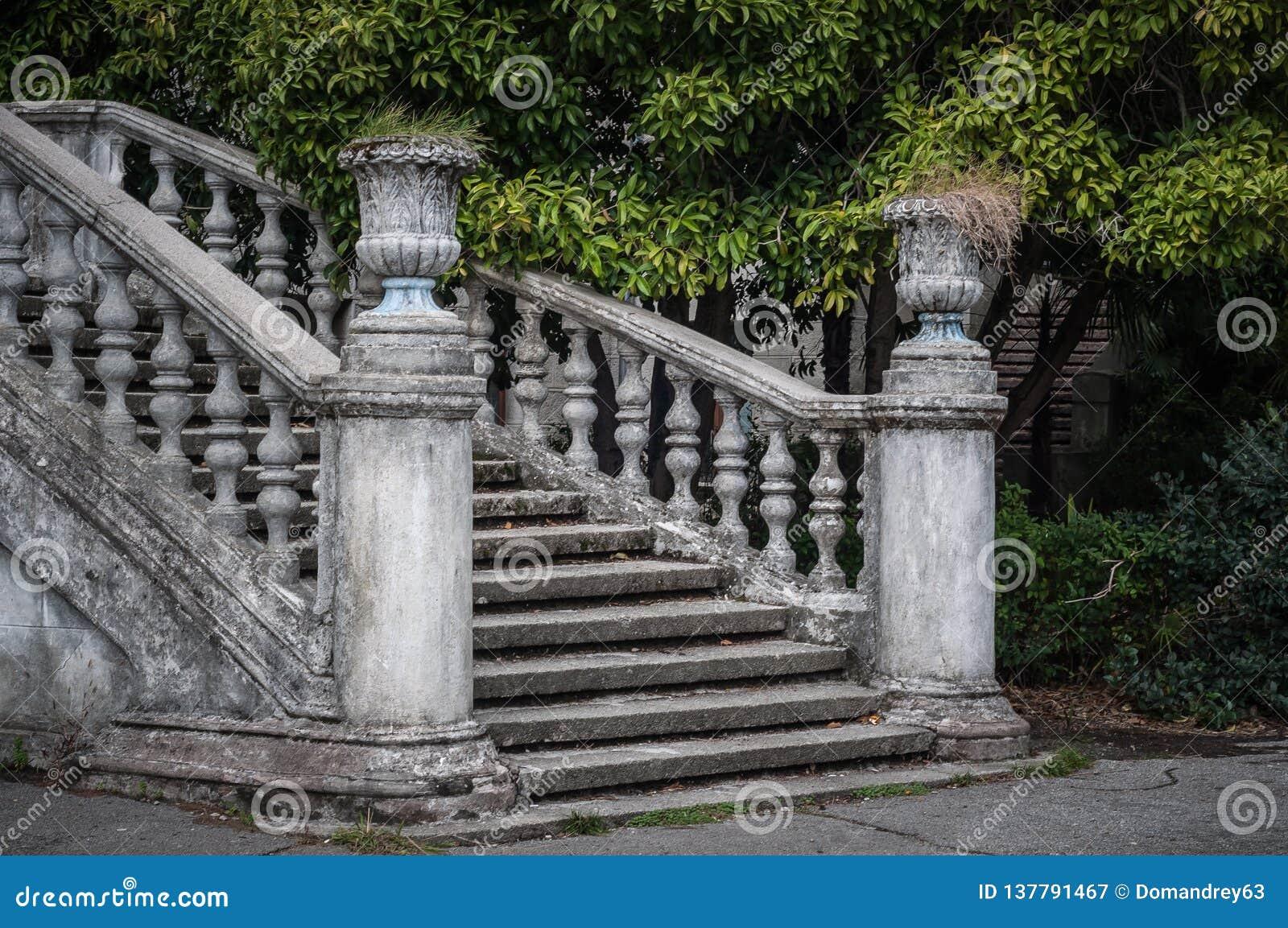 Escalier antique avec les balustres en pierre dans la perspective de la végétation verte