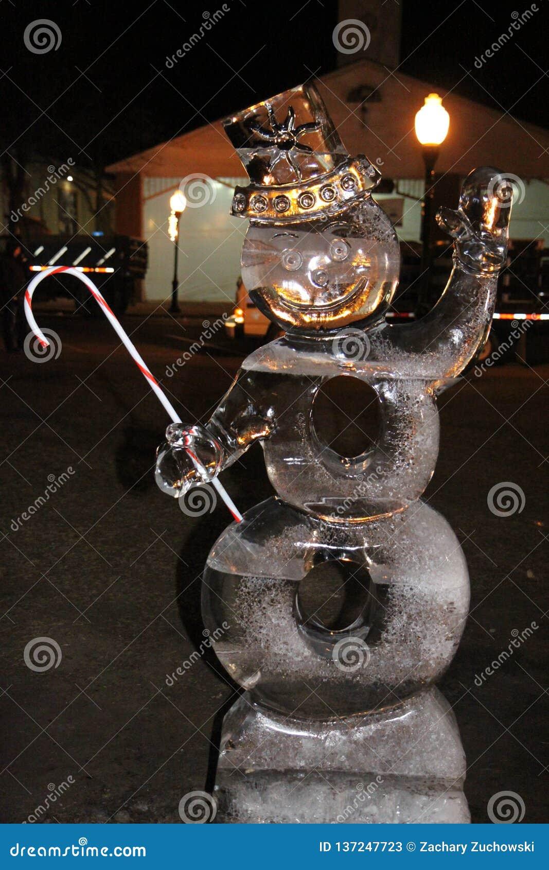 Escarchado la escultura de hielo del muñeco de nieve con un bastón de caramelo